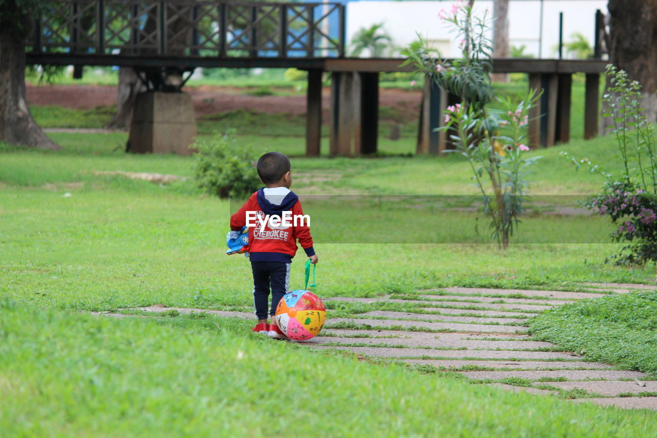 Rear View Of Boy Playing On Field