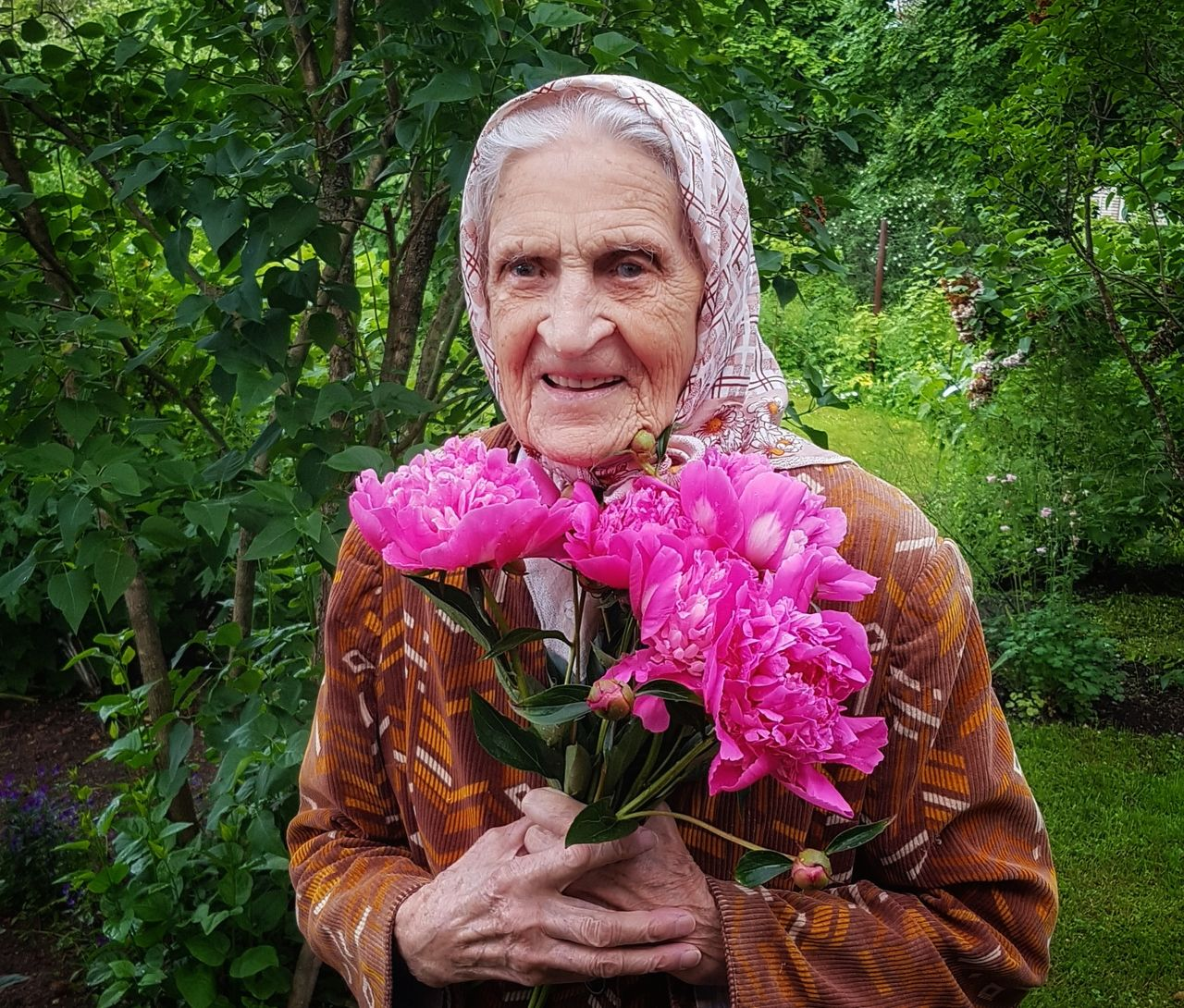 Portrait Of Senior Woman With Pink Flowers At Park