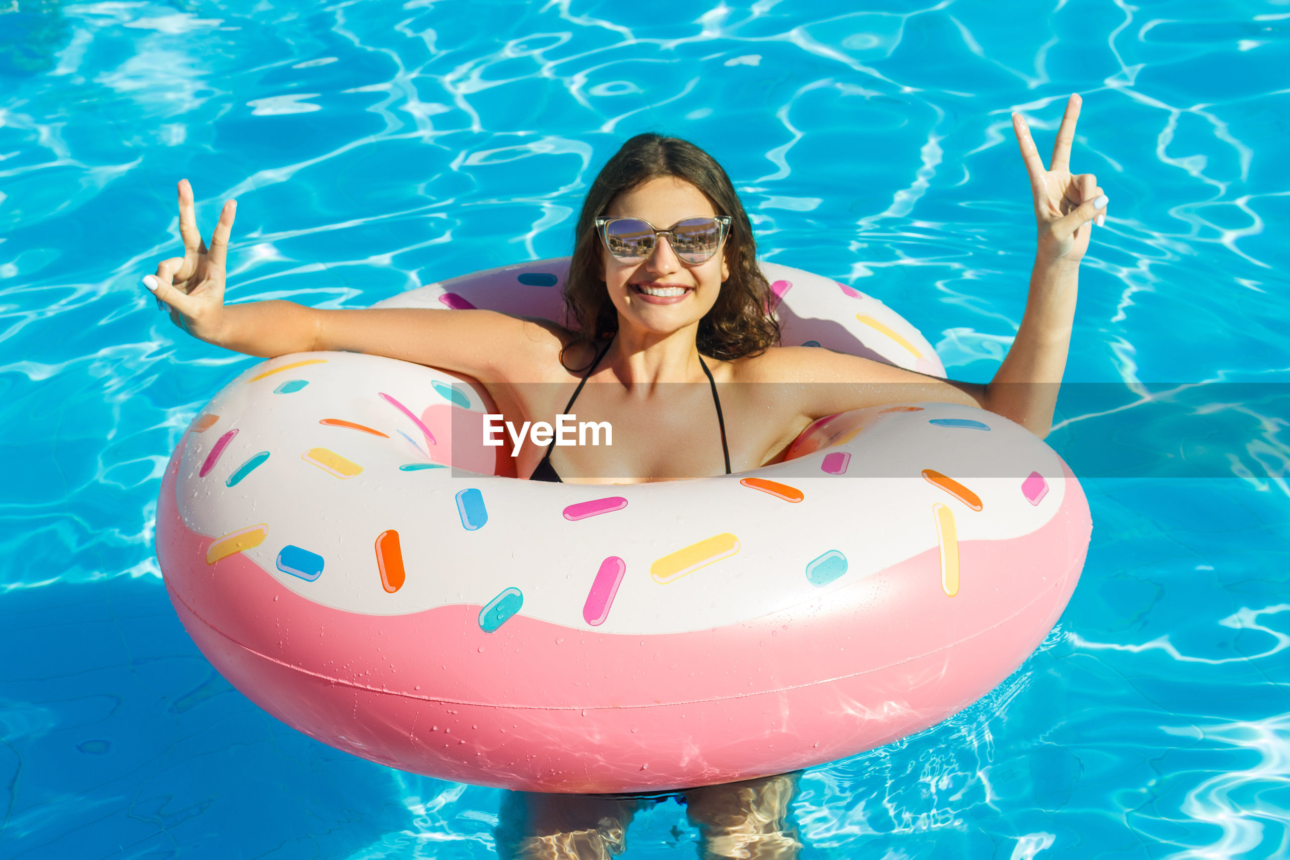 Smiling young woman enjoying in swimming pool with inflatable ring during summer