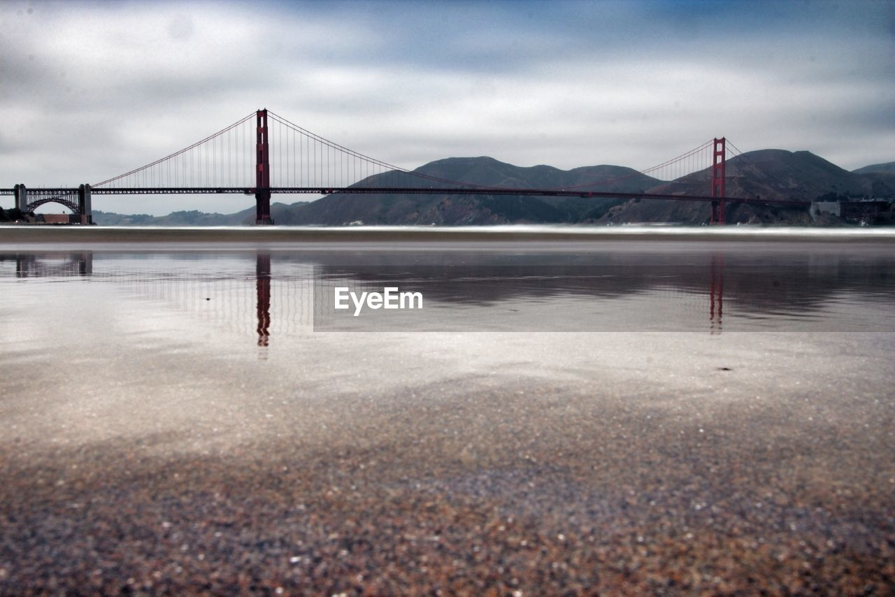 Reflection of golden gate bridge on sea against sky