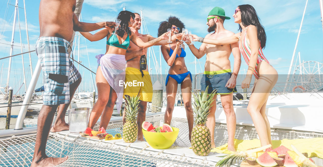 Smiling Friends Raising Toast While Standing In Ship
