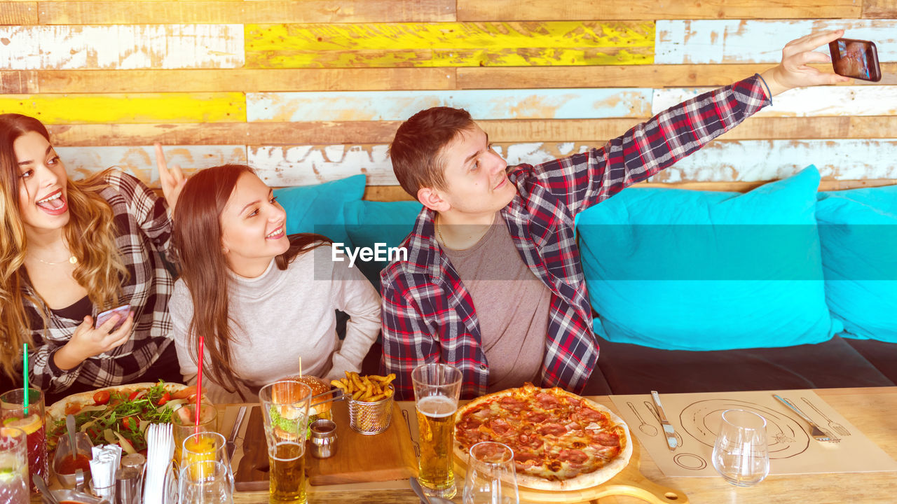 Man with happy friends taking selfie at restaurant