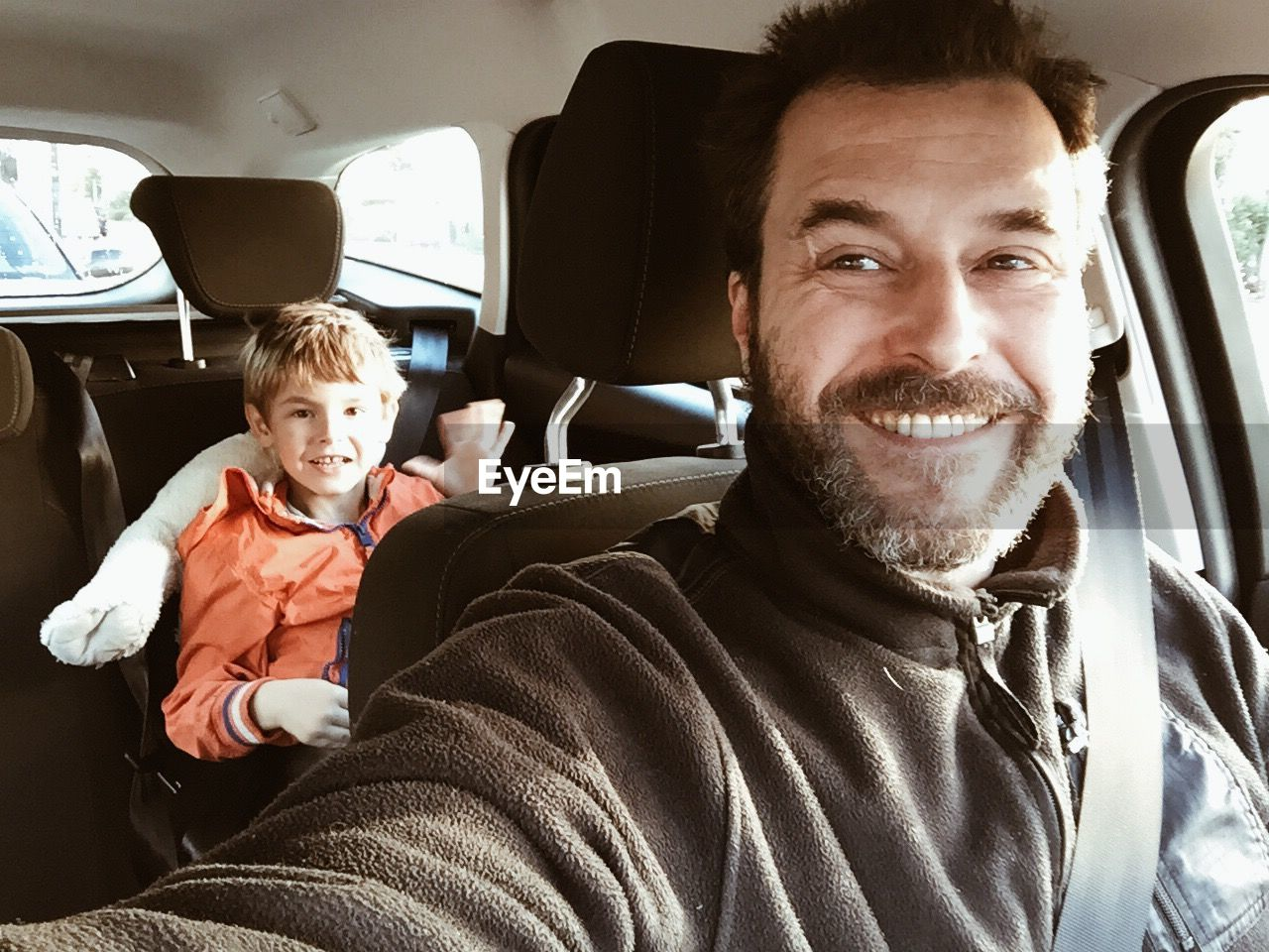 Smiling father in car with son sitting at back seat