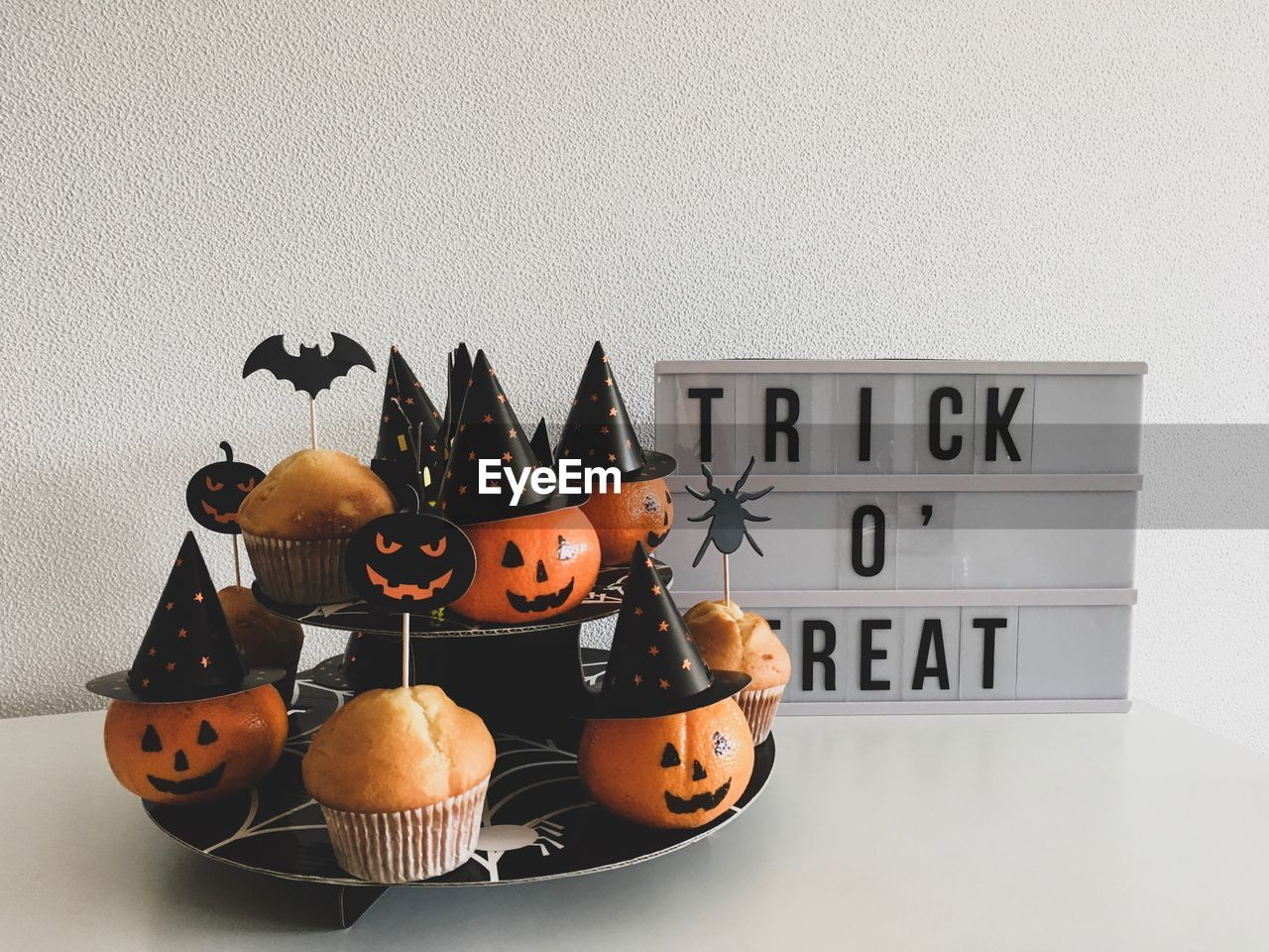 Close-up of pumpkins and cupcakes with text against white background