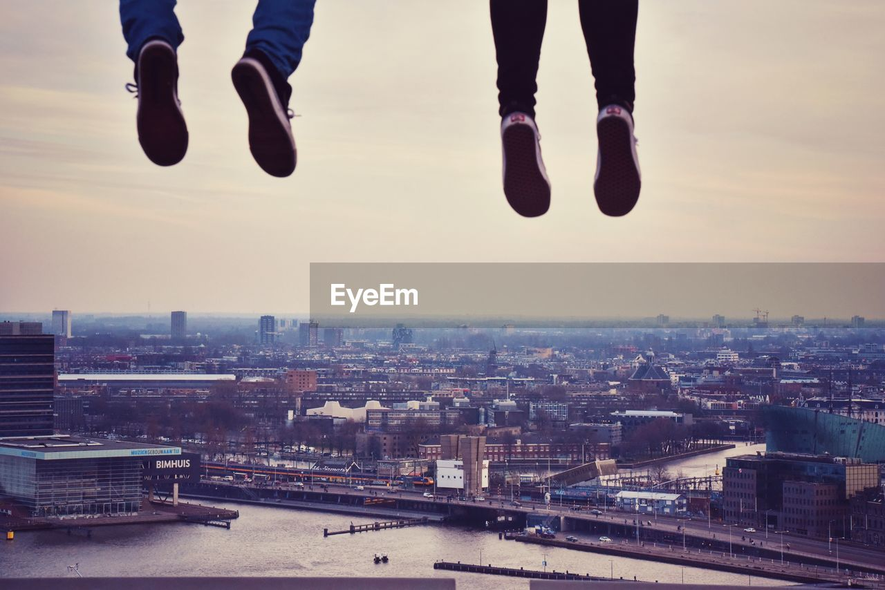 sky, architecture, built structure, building exterior, mid-air, city, low section, body part, real people, human body part, nature, water, cityscape, human leg, one person, shoe, lifestyles, leisure activity, cloud - sky, outdoors, human foot, human limb