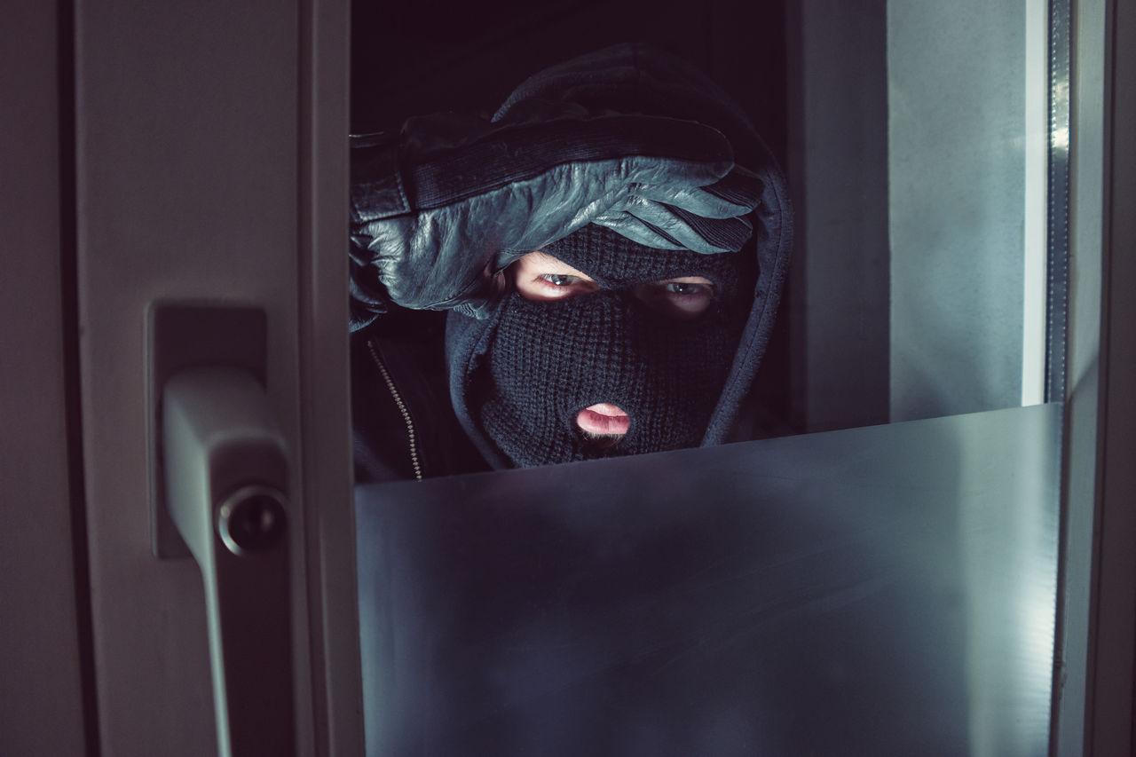 Portrait Of Burglar Looking Through Door