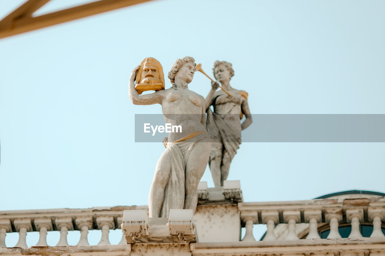 LOW ANGLE VIEW OF STATUES AGAINST BUILDING AGAINST SKY
