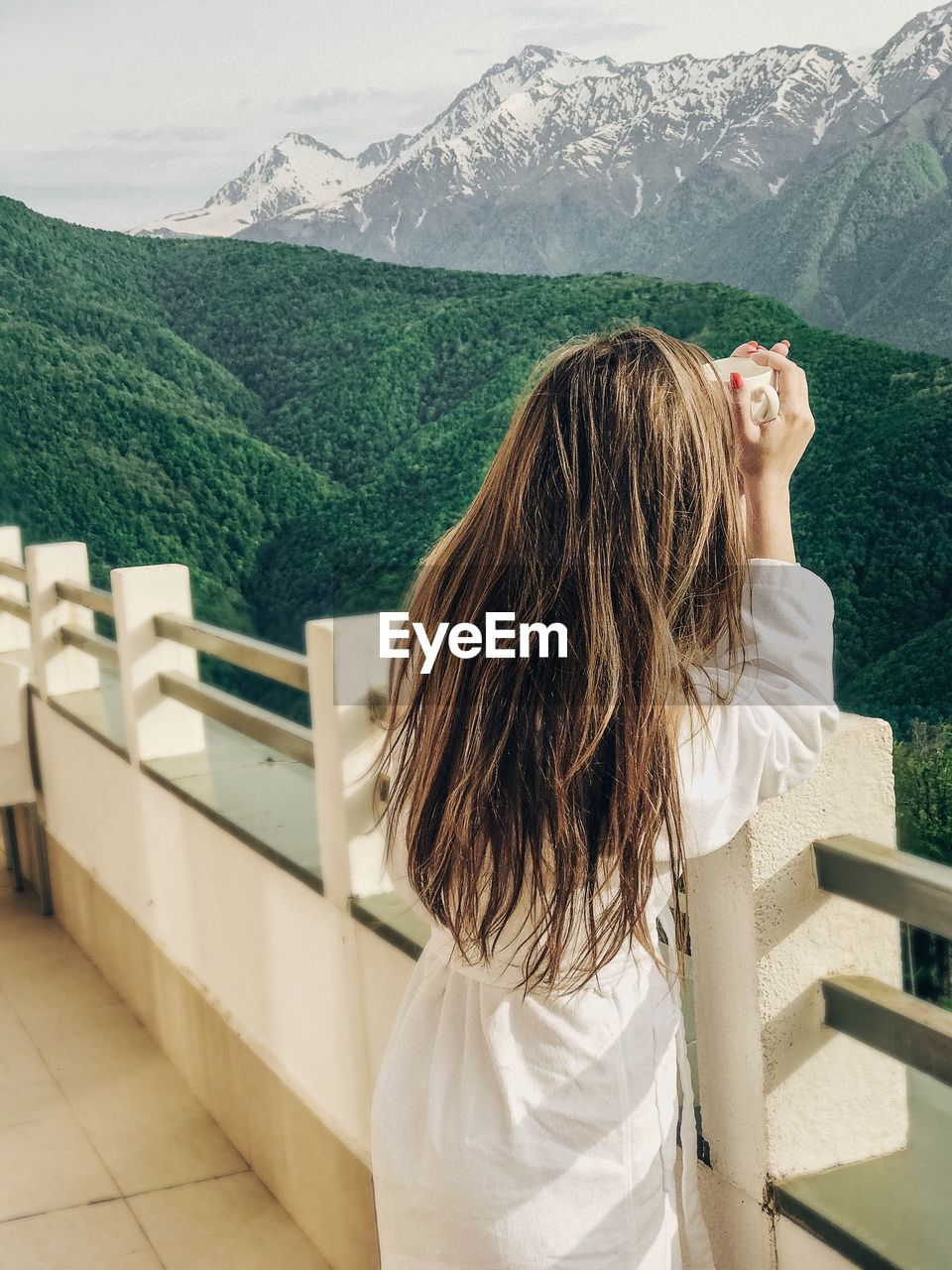 Rear View Of Woman Standing On Railing Against Mountains