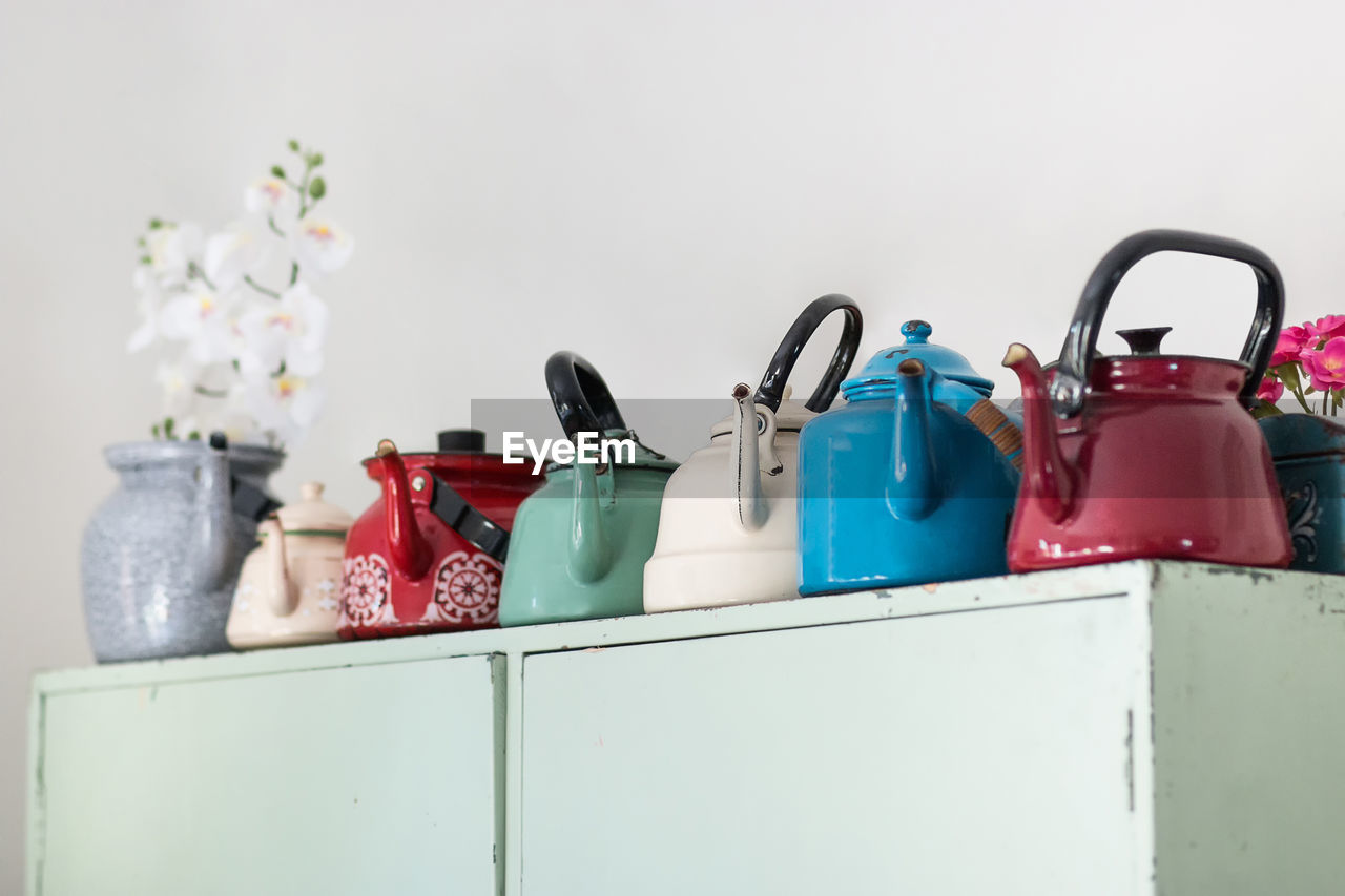 Close-up of multi colored kettles on shelf