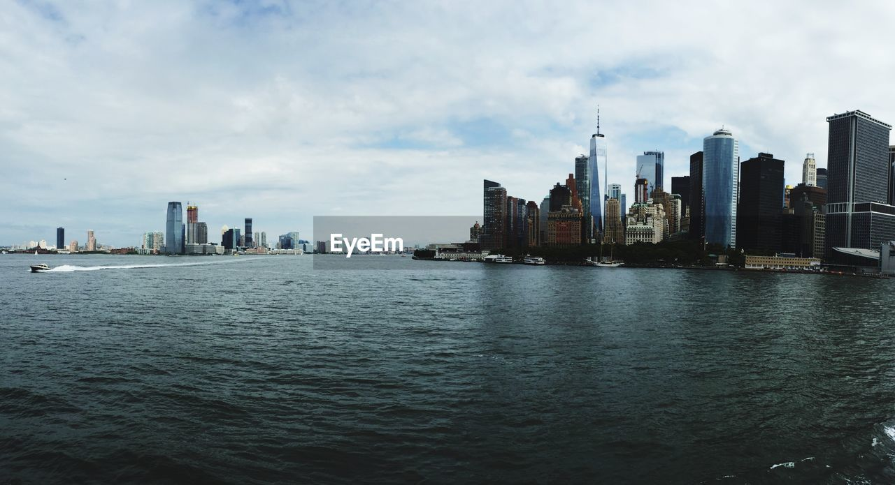 SEA BY BUILDINGS IN CITY AGAINST SKY