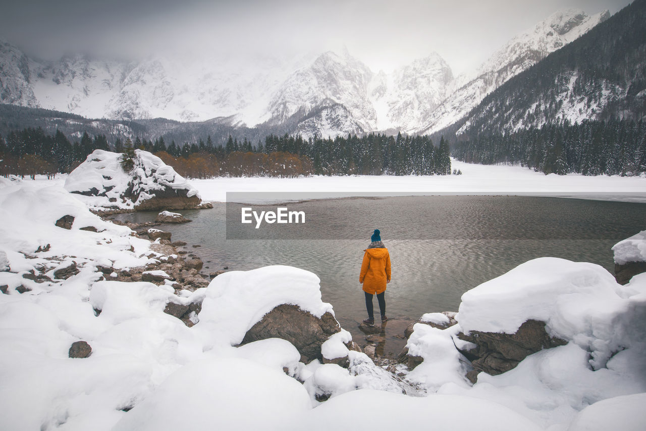 snow, cold temperature, winter, mountain, scenics - nature, beauty in nature, real people, one person, rear view, nature, leisure activity, tranquil scene, tranquility, warm clothing, covering, lifestyles, full length, clothing, non-urban scene, snowcapped mountain, mountain range, outdoors