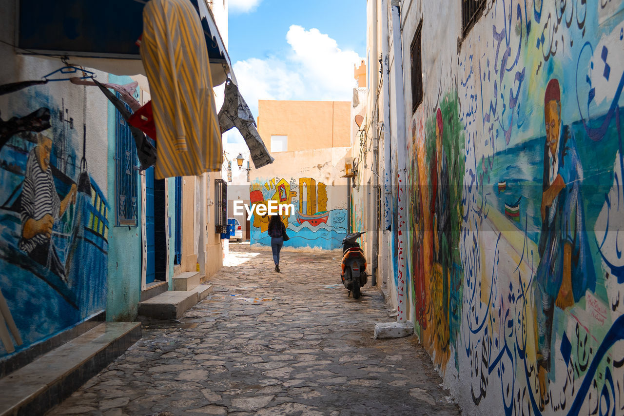 REAR VIEW OF WOMAN ON STREET AMIDST BUILDINGS