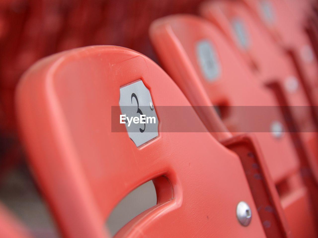 Close-up of number 3 on orange chair at stadium
