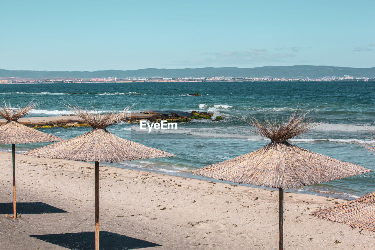 sea, water, beach, sky, land, scenics - nature, thatched roof, nature, beauty in nature, day, tranquility, no people, tranquil scene, roof, sand, horizon over water, parasol, horizon, travel destinations, outdoors