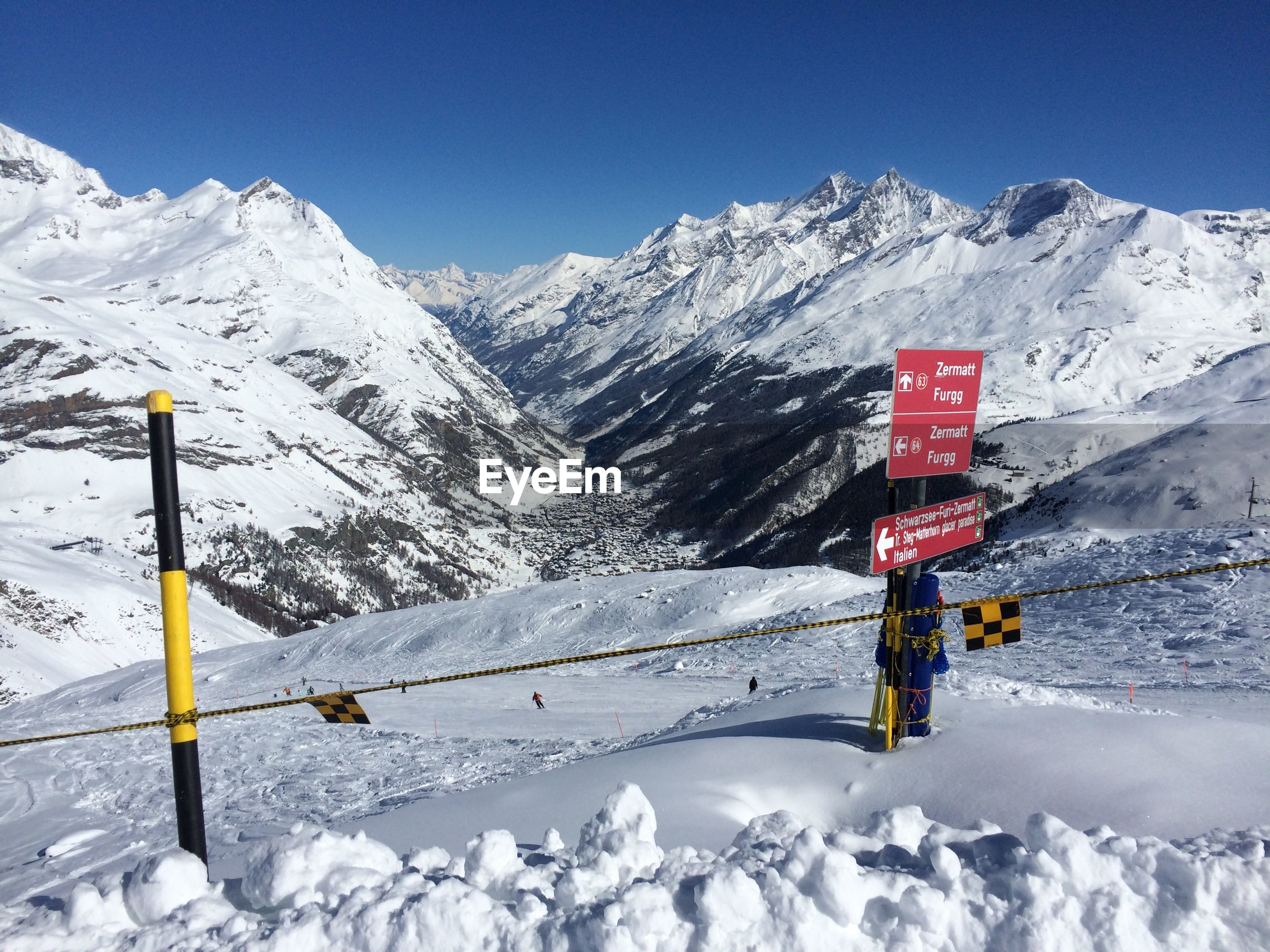 Directional sign on snowcapped mountain