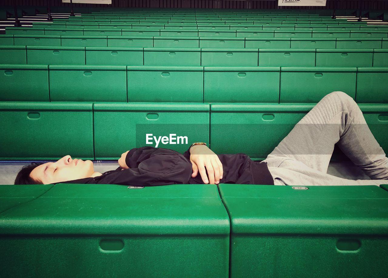 Man sleeping on green seat