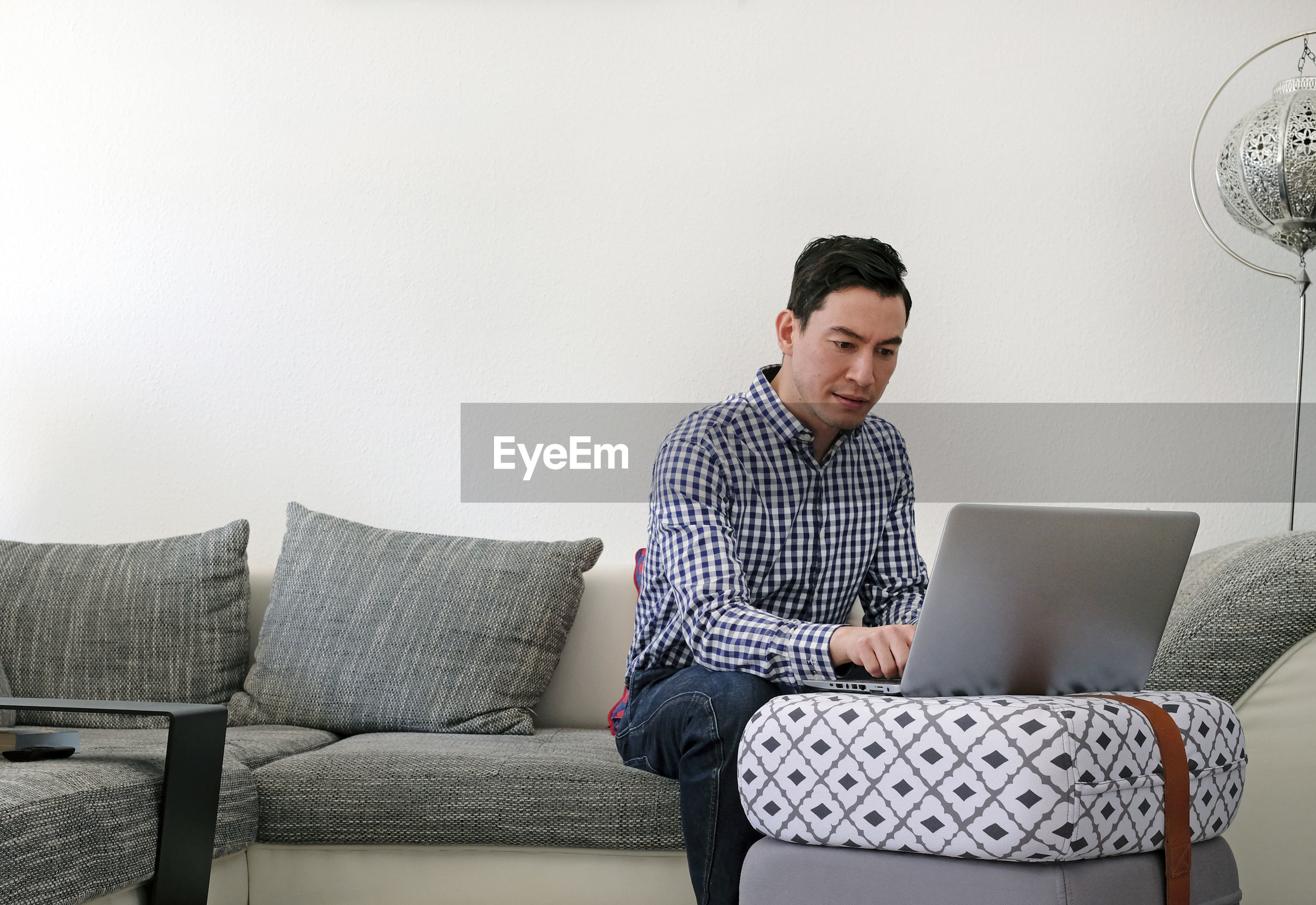 Man using mobile phone while sitting on sofa