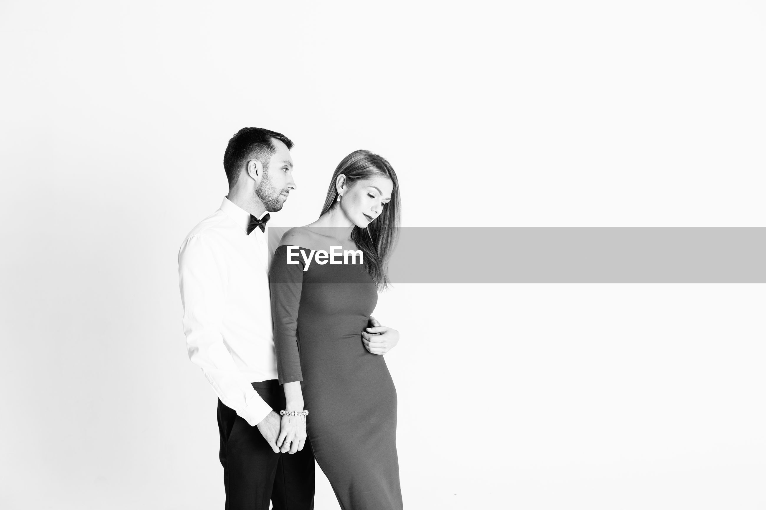 Elegant couple standing against white background