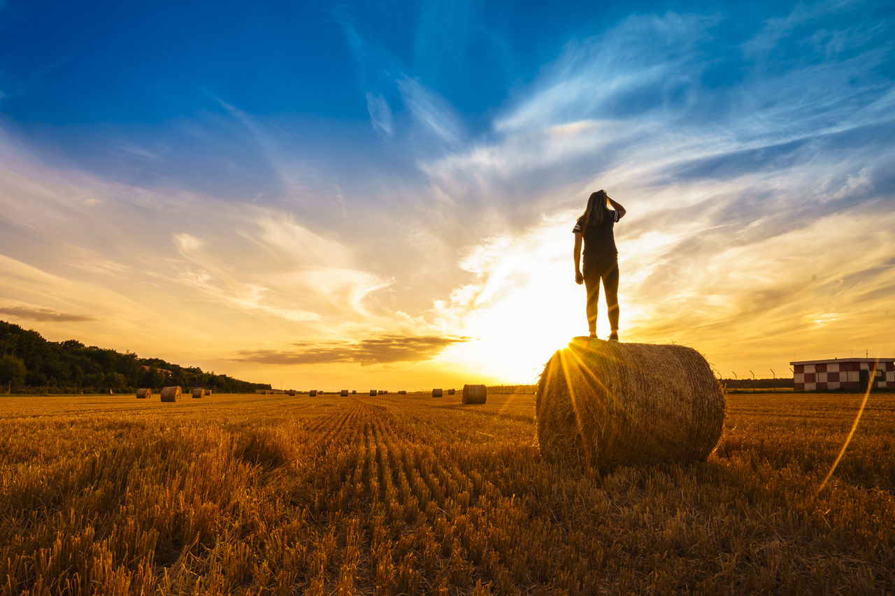 Woman Standing On Hay Bale Against Sky During Sunset