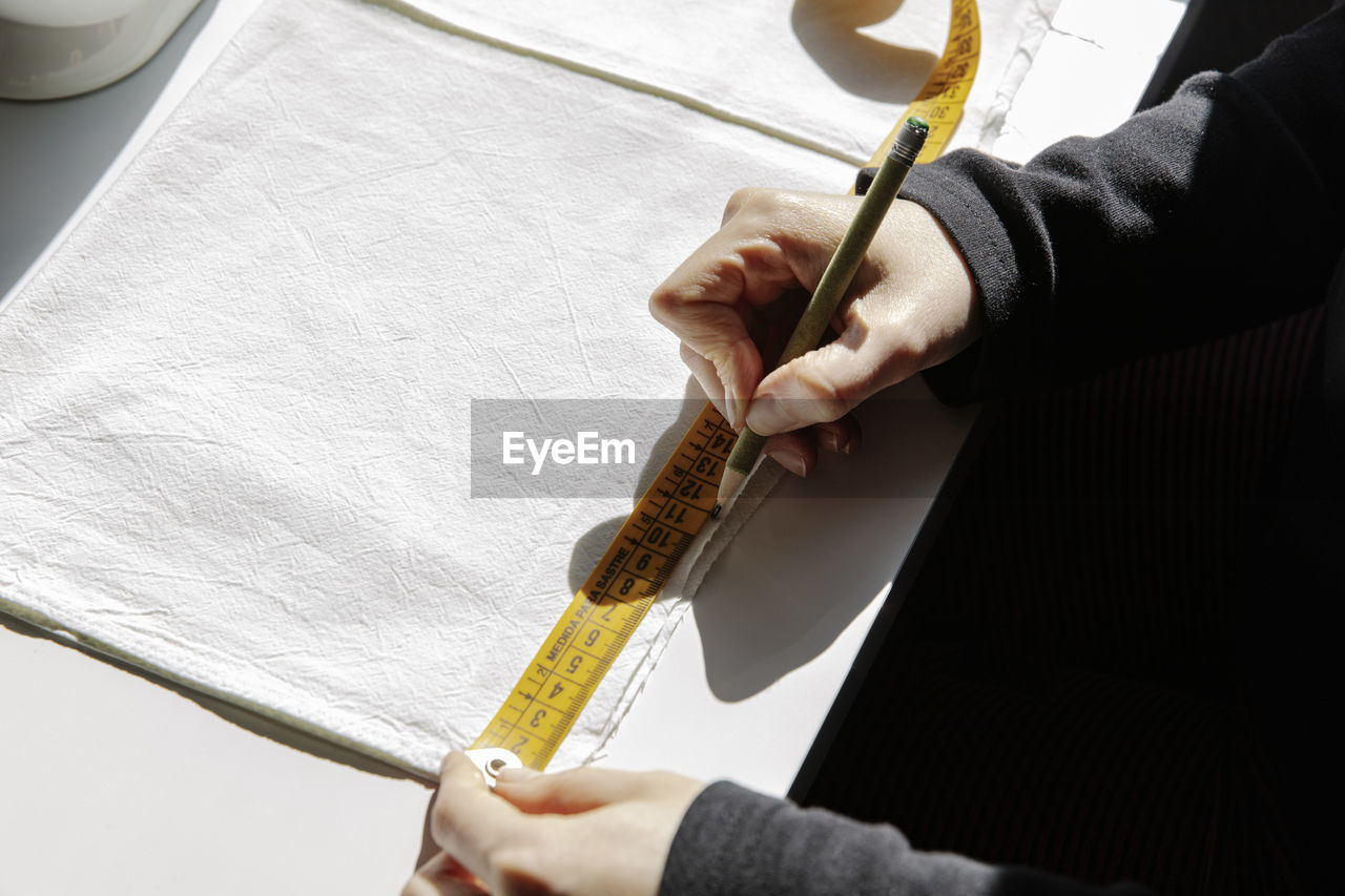HIGH ANGLE VIEW OF HAND HOLDING PAPER WITH TEXT