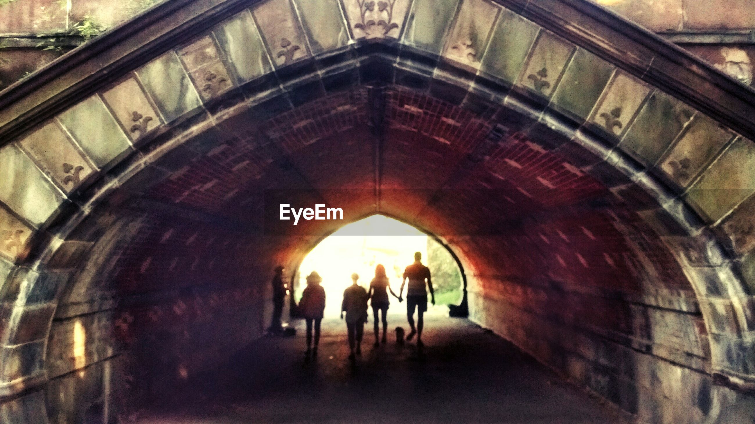 indoors, lifestyles, men, tunnel, full length, arch, leisure activity, person, walking, architecture, rear view, built structure, ceiling, togetherness, the way forward, standing, wall - building feature, illuminated