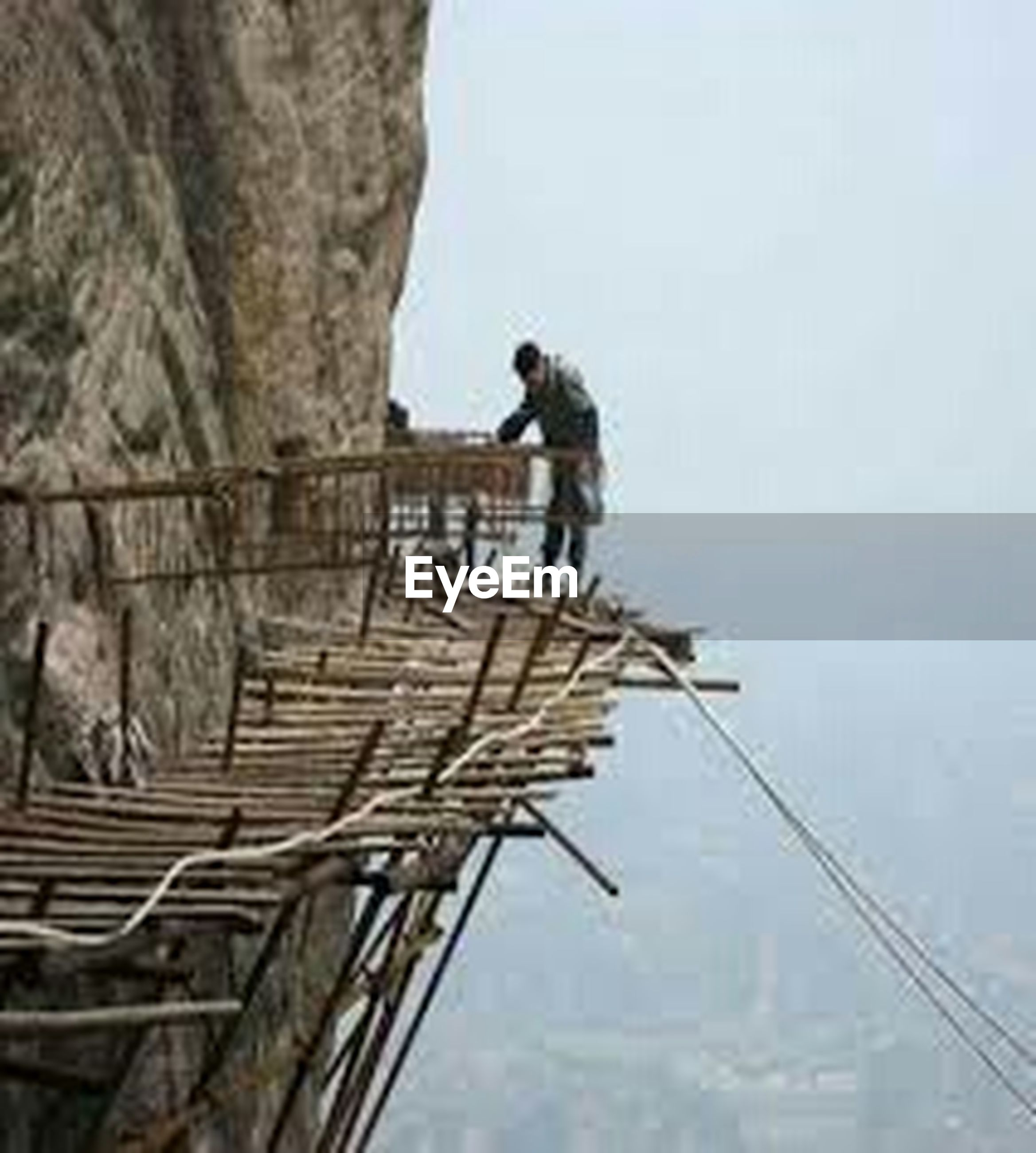 low angle view, animal themes, sky, clear sky, bird, one animal, wildlife, animals in the wild, built structure, perching, day, full length, architecture, outdoors, nature, railing, rope, leisure activity