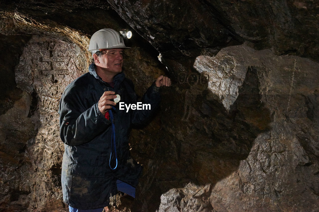 Man Wearing Helmet Standing In Cave