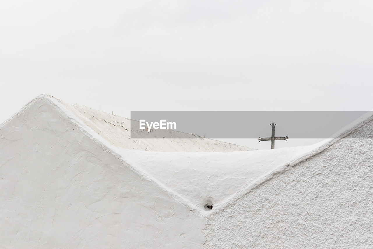 sky, snow, religion, day, cold temperature, copy space, architecture, cross, winter, nature, belief, spirituality, no people, built structure, white color, scenics - nature, tranquility, clear sky, outdoors, snowcapped mountain