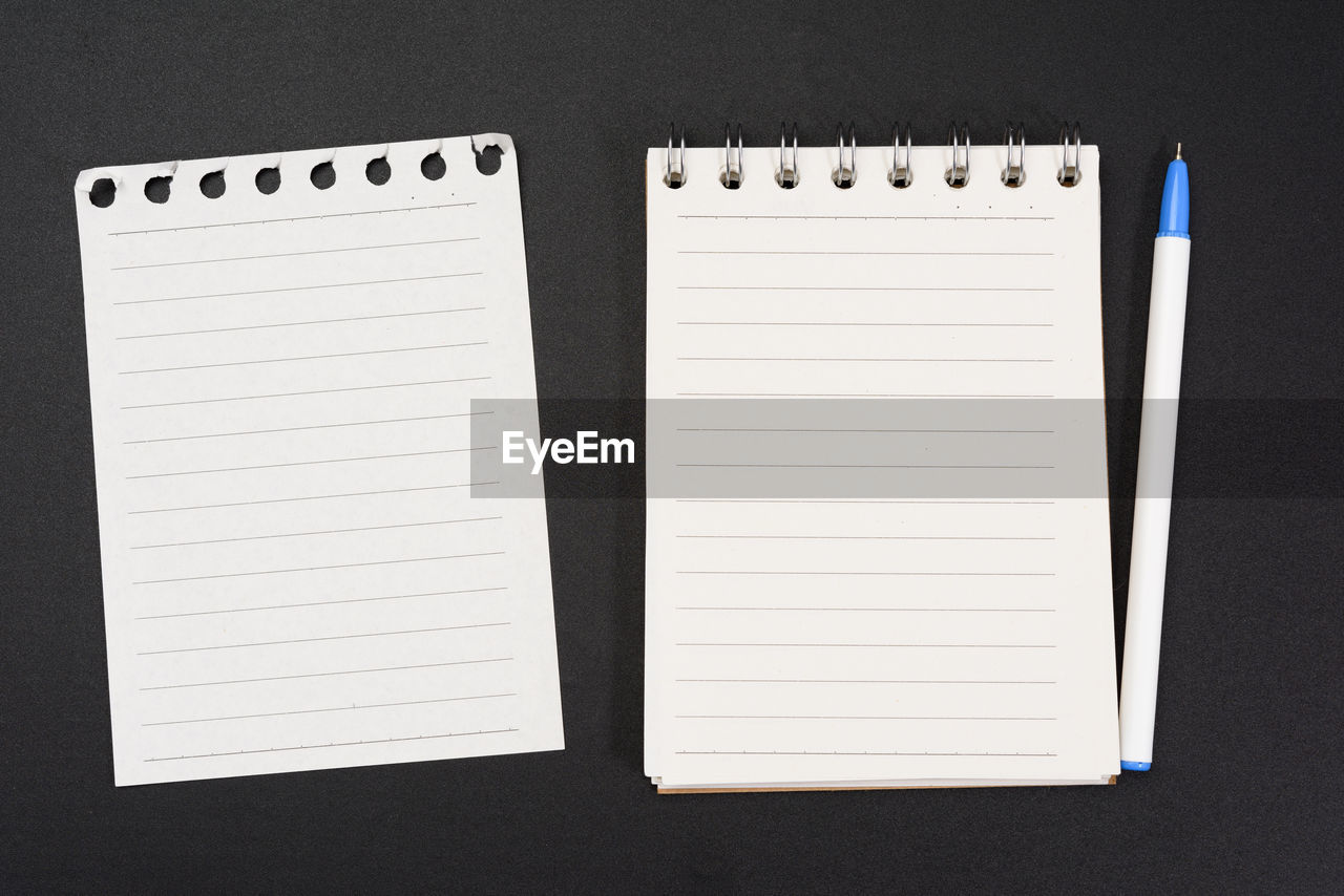 Notebook with white sheets in a line on a black background, close up