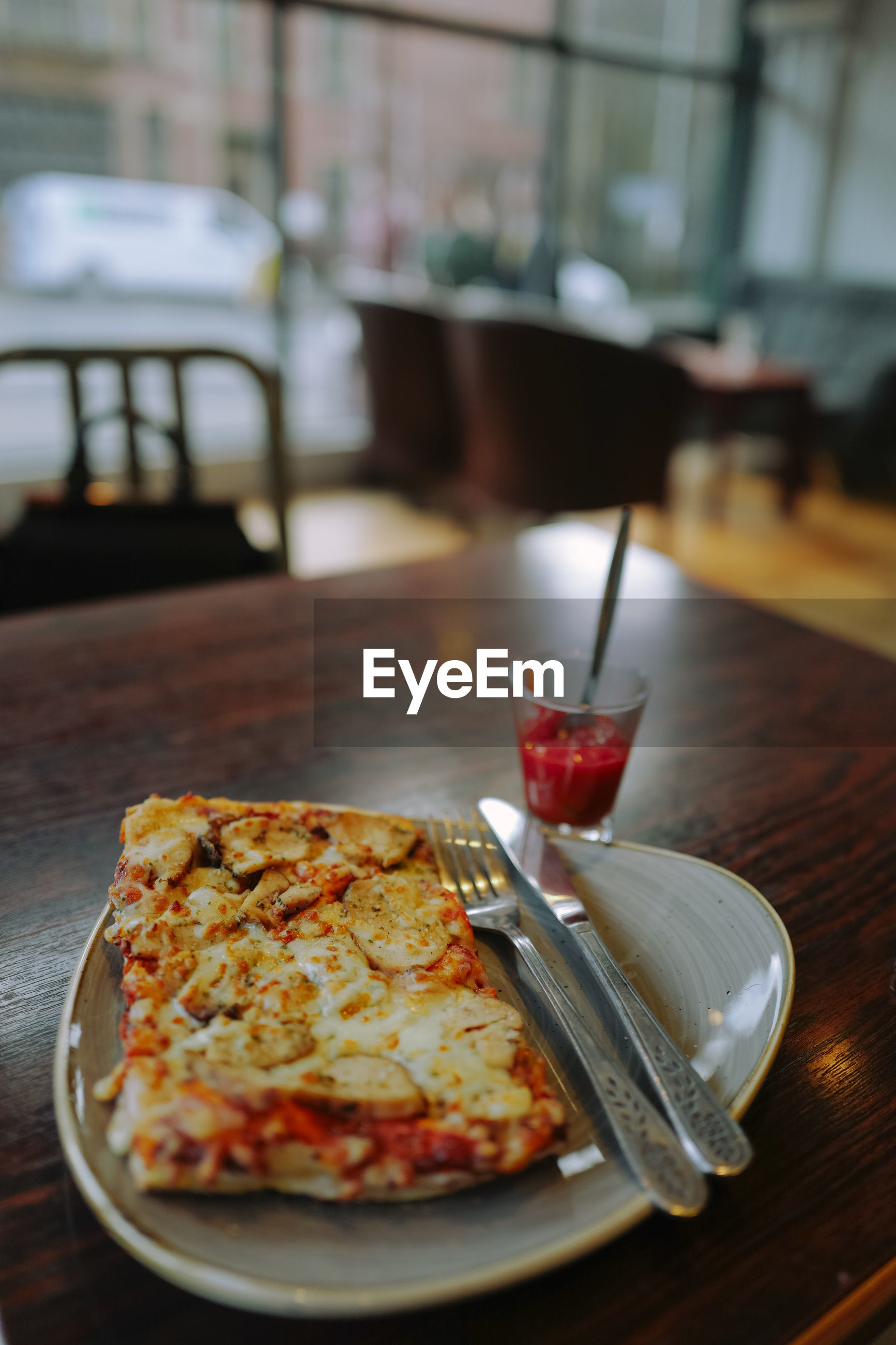High angle close-up of pizza slice in plate on wooden table at restaurant