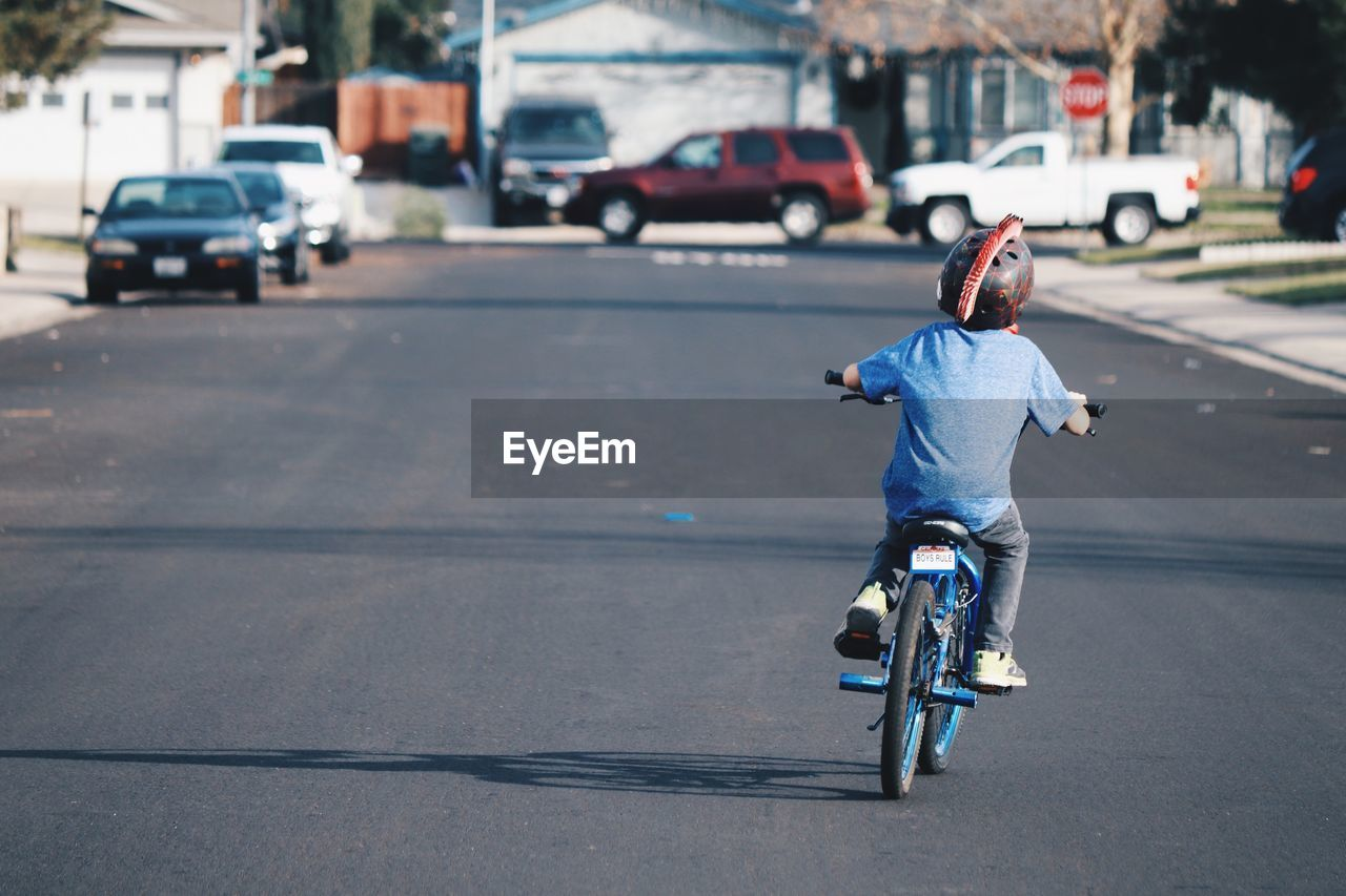 FULL LENGTH REAR VIEW OF BOY RIDING BICYCLE ON ROAD