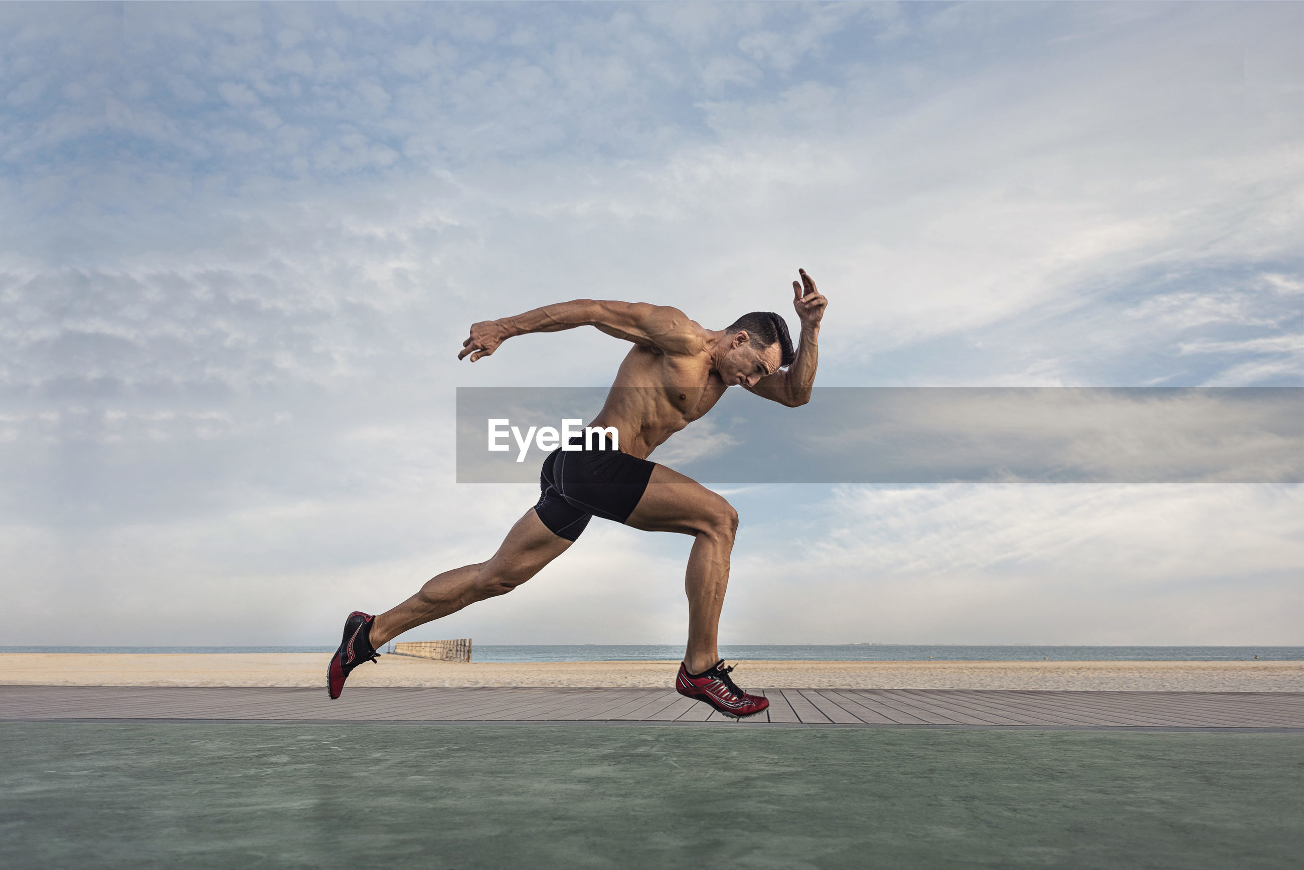 Side view of shirtless man taking running stance against sky