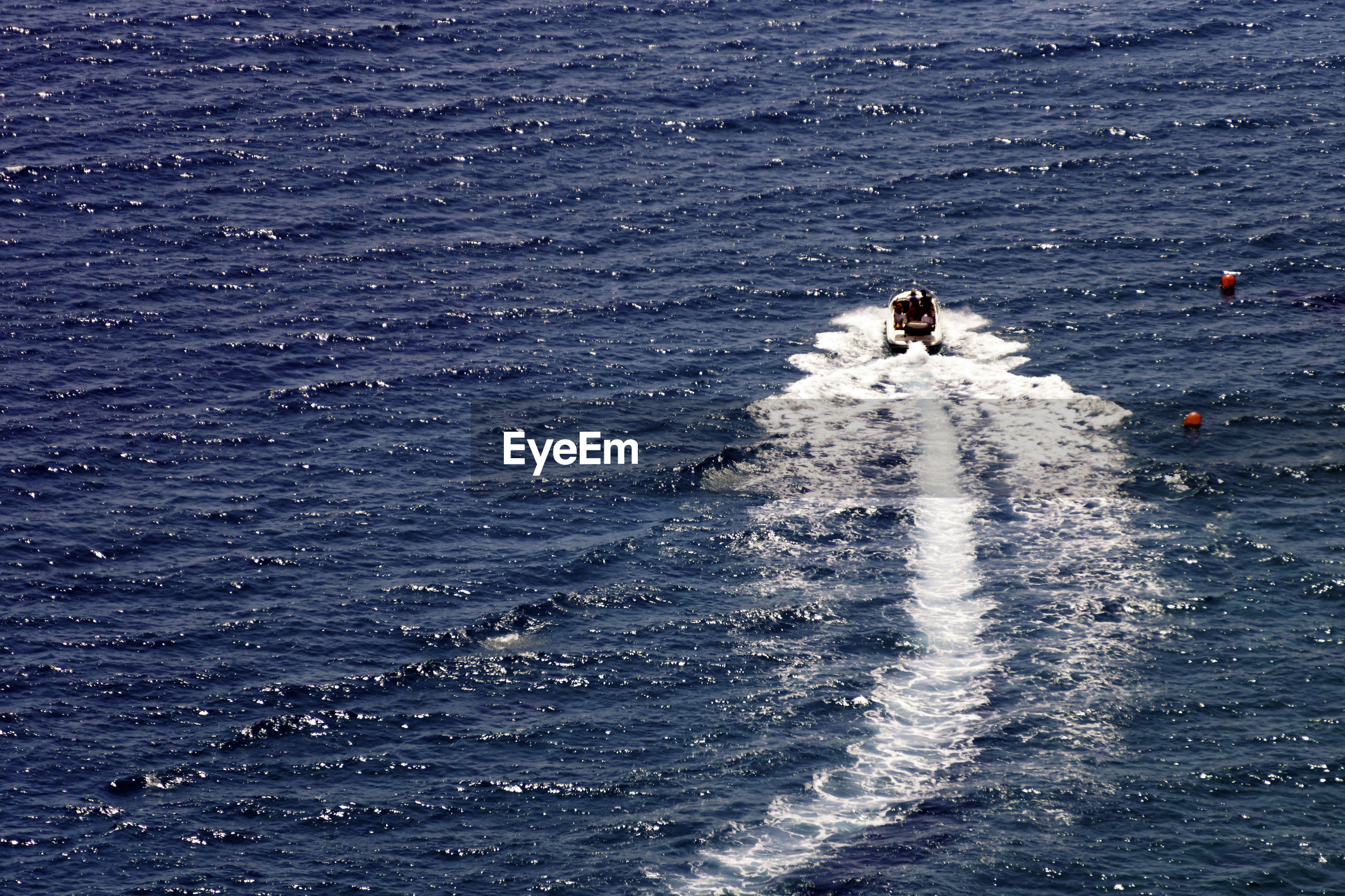 Distant view of people on jet boat at sea
