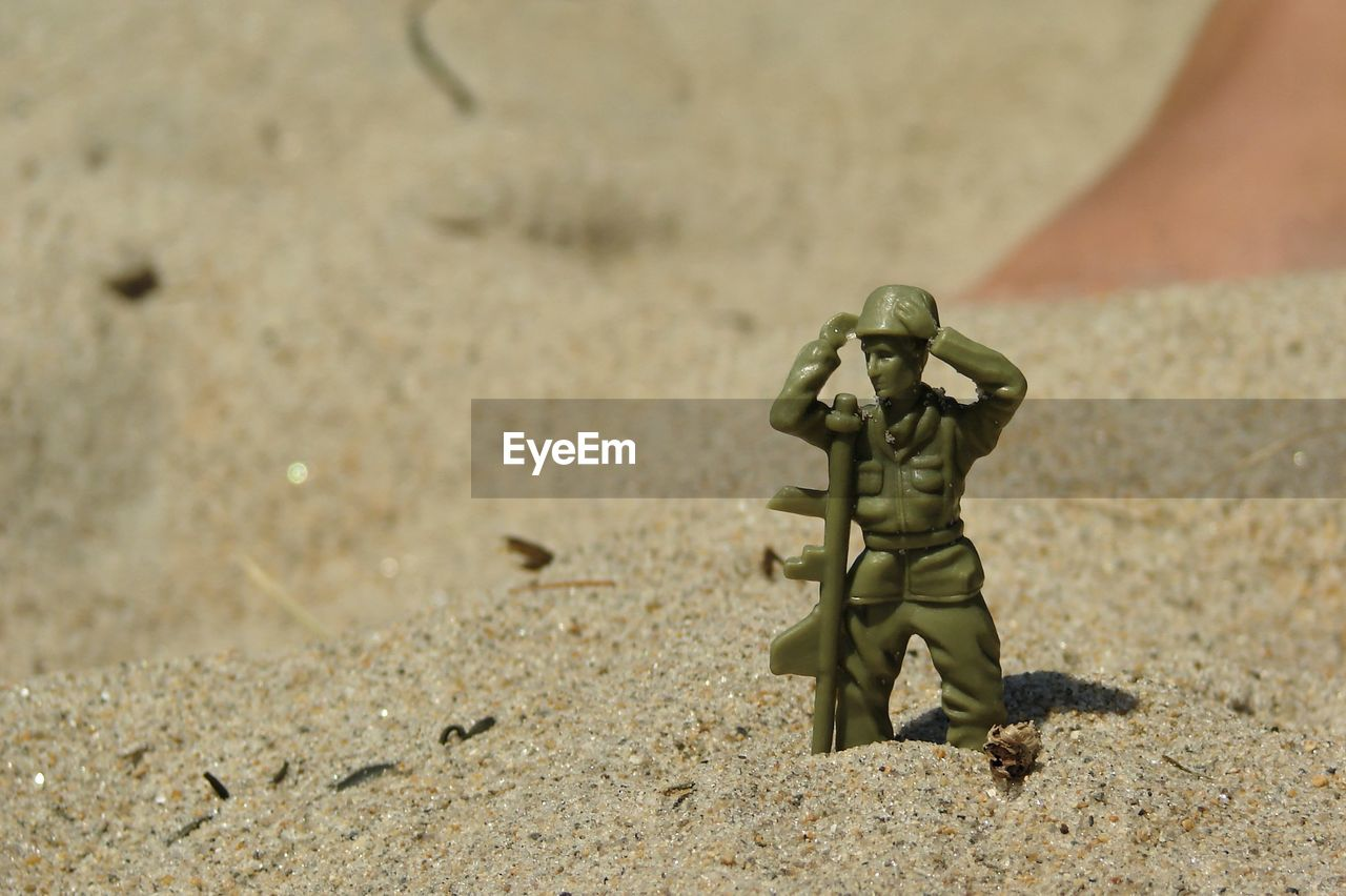 Close-Up Of Soldier Figurine On Sand During Sunny Day