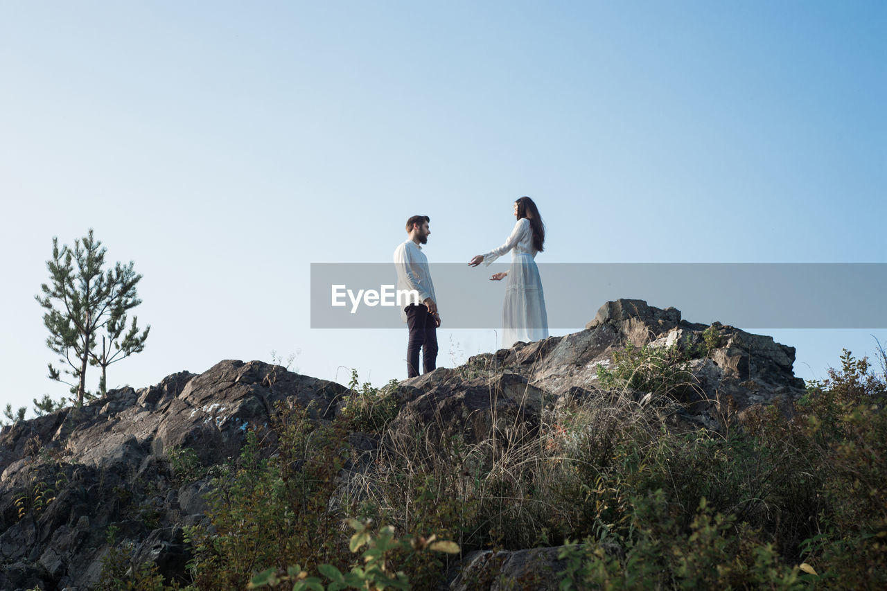 sky, two people, real people, leisure activity, nature, women, rock, casual clothing, lifestyles, togetherness, standing, rock - object, clear sky, solid, young adult, bonding, adult, young men, people, men, couple - relationship, outdoors