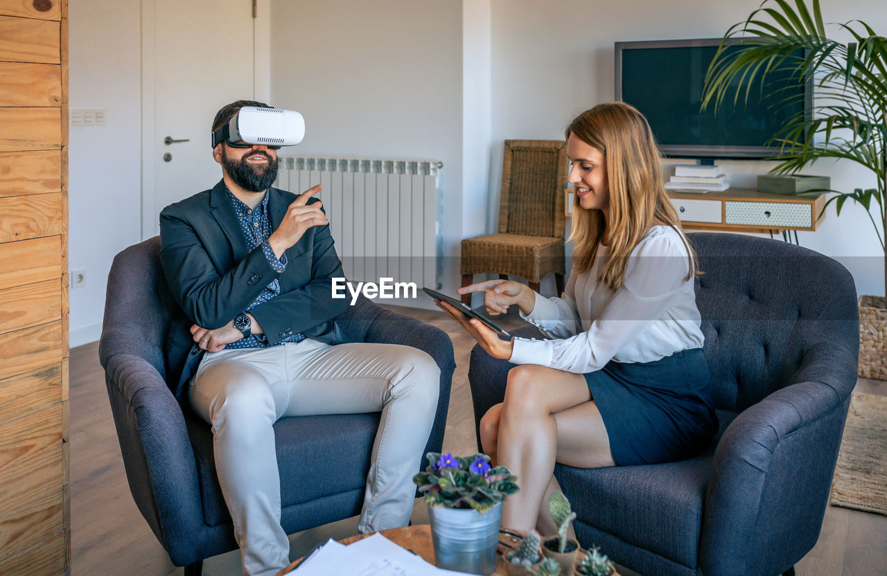 Businessman using virtual reality simulator while colleague holding laptop