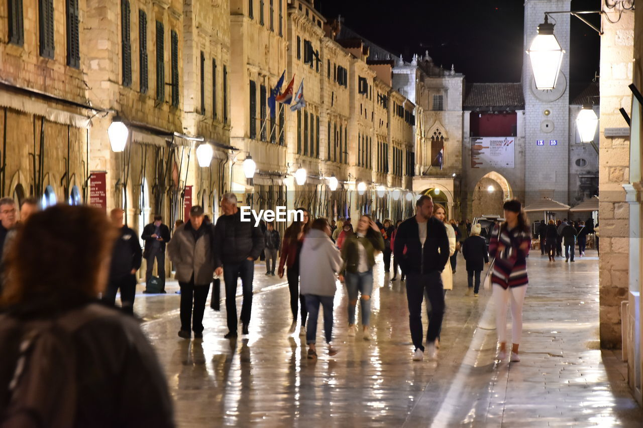 PEOPLE WALKING ON ILLUMINATED STREET IN CITY