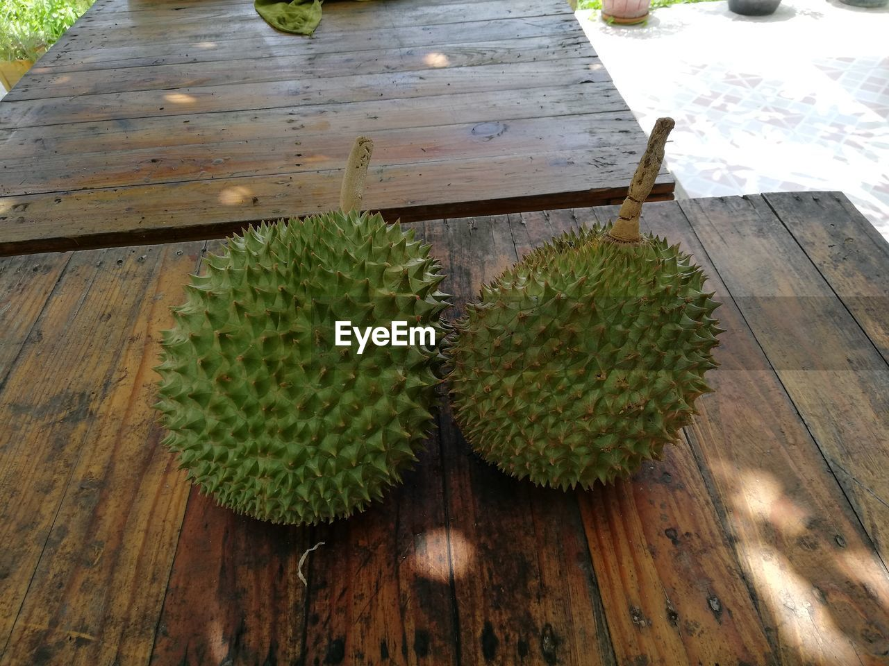 green color, wood - material, food and drink, table, no people, food, fruit, high angle view, healthy eating, close-up, freshness, wellbeing, day, still life, tropical fruit, outdoors, thorn, plant, spiked, spiky