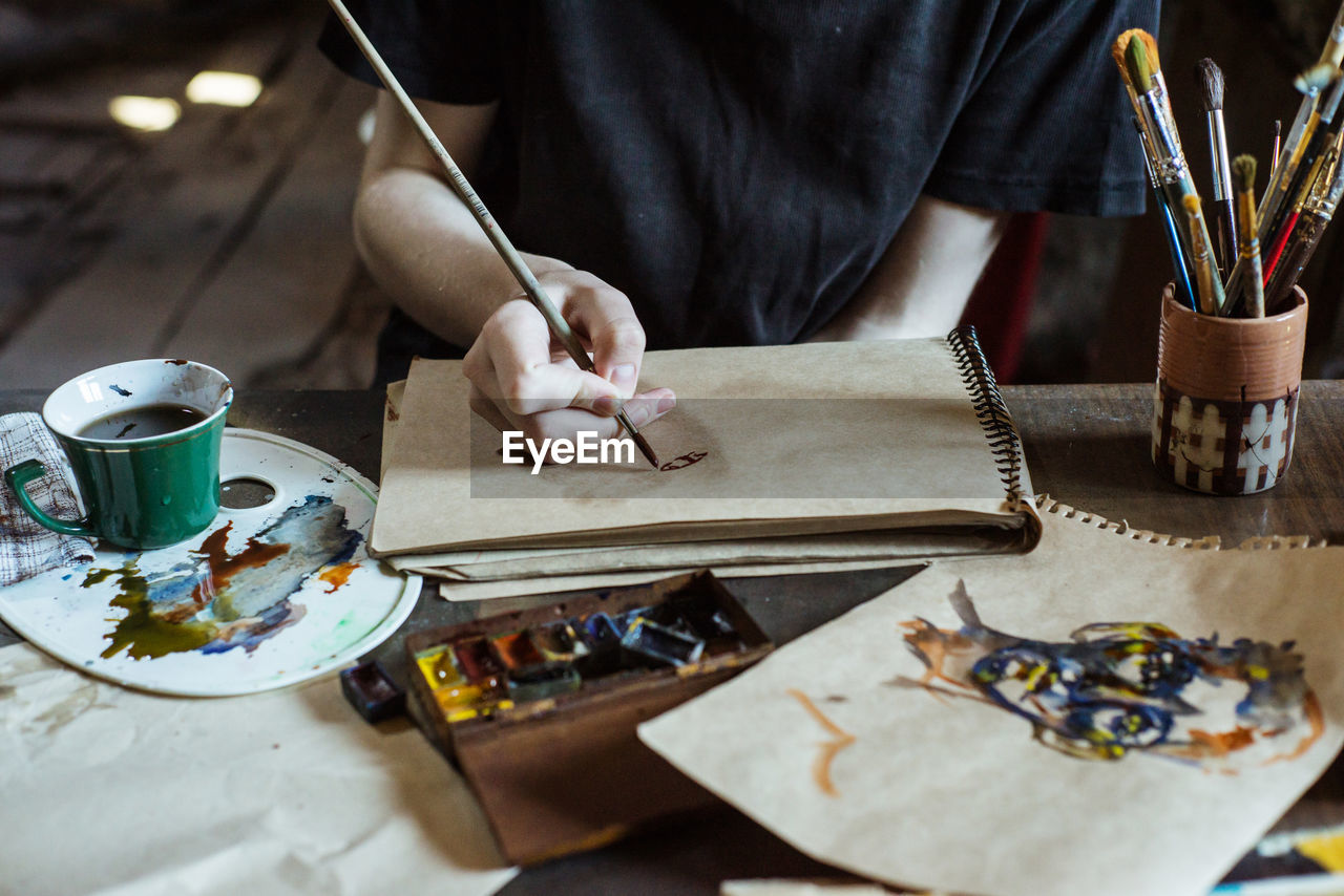 one person, art and craft, table, occupation, real people, creativity, craft, indoors, holding, workshop, human hand, brush, skill, hand, midsection, selective focus, paintbrush, working, paper, art and craft equipment, workbench