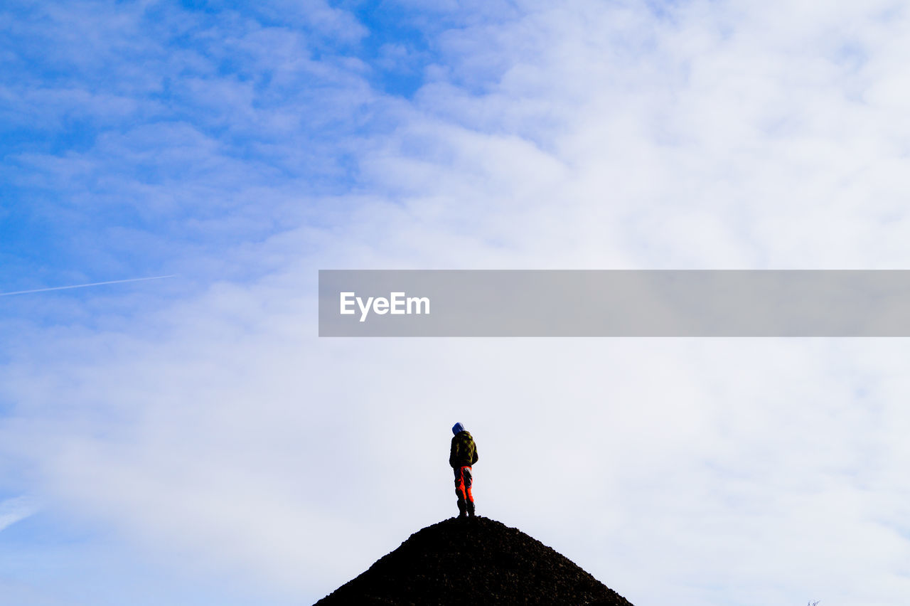 Low Angle View Of Man On Top Of Mountain