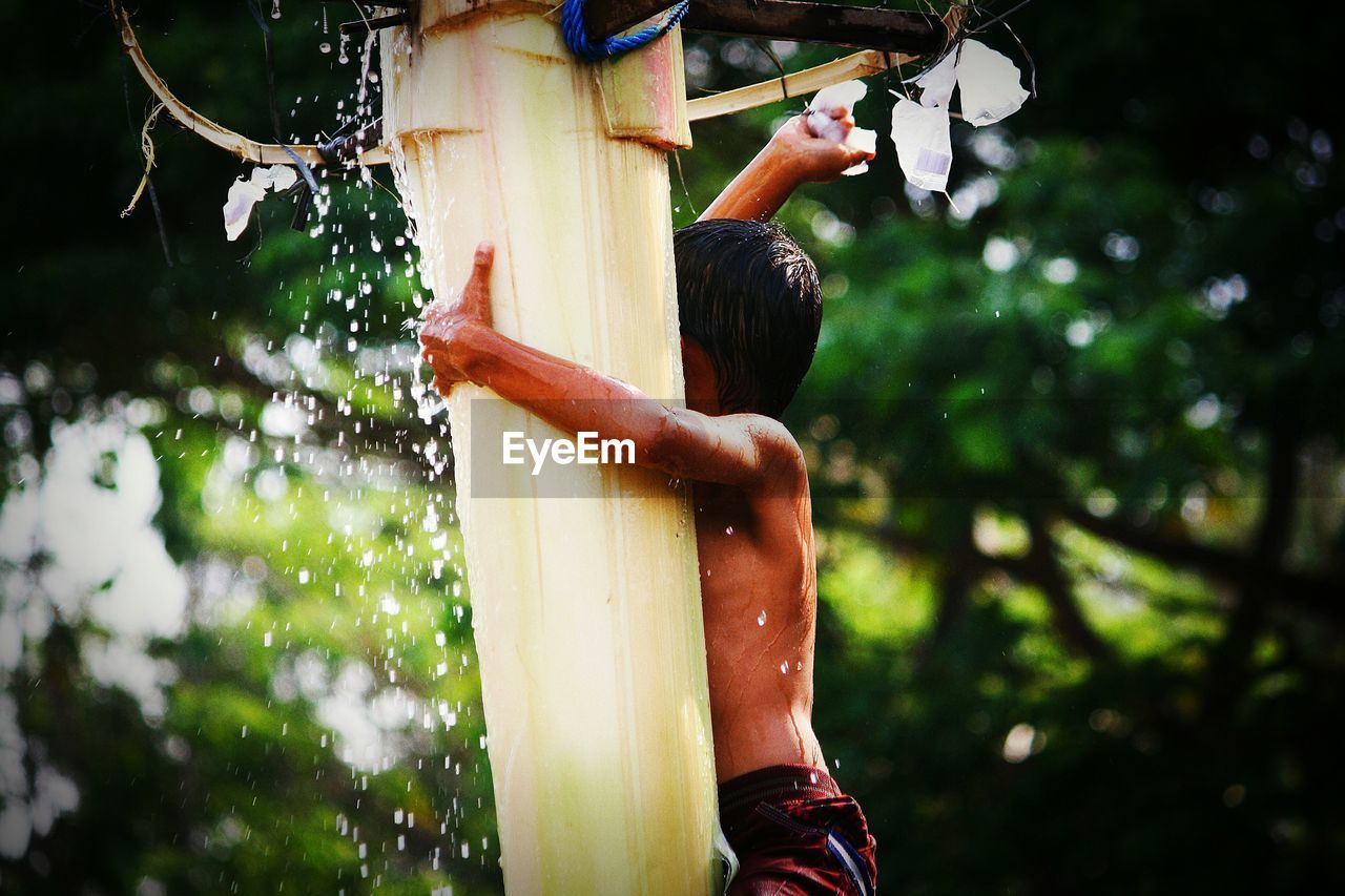 focus on foreground, real people, nature, day, water, plant, tree, motion, one person, human body part, outdoors, holding, lifestyles, body part, men, leisure activity, land, wet, human limb