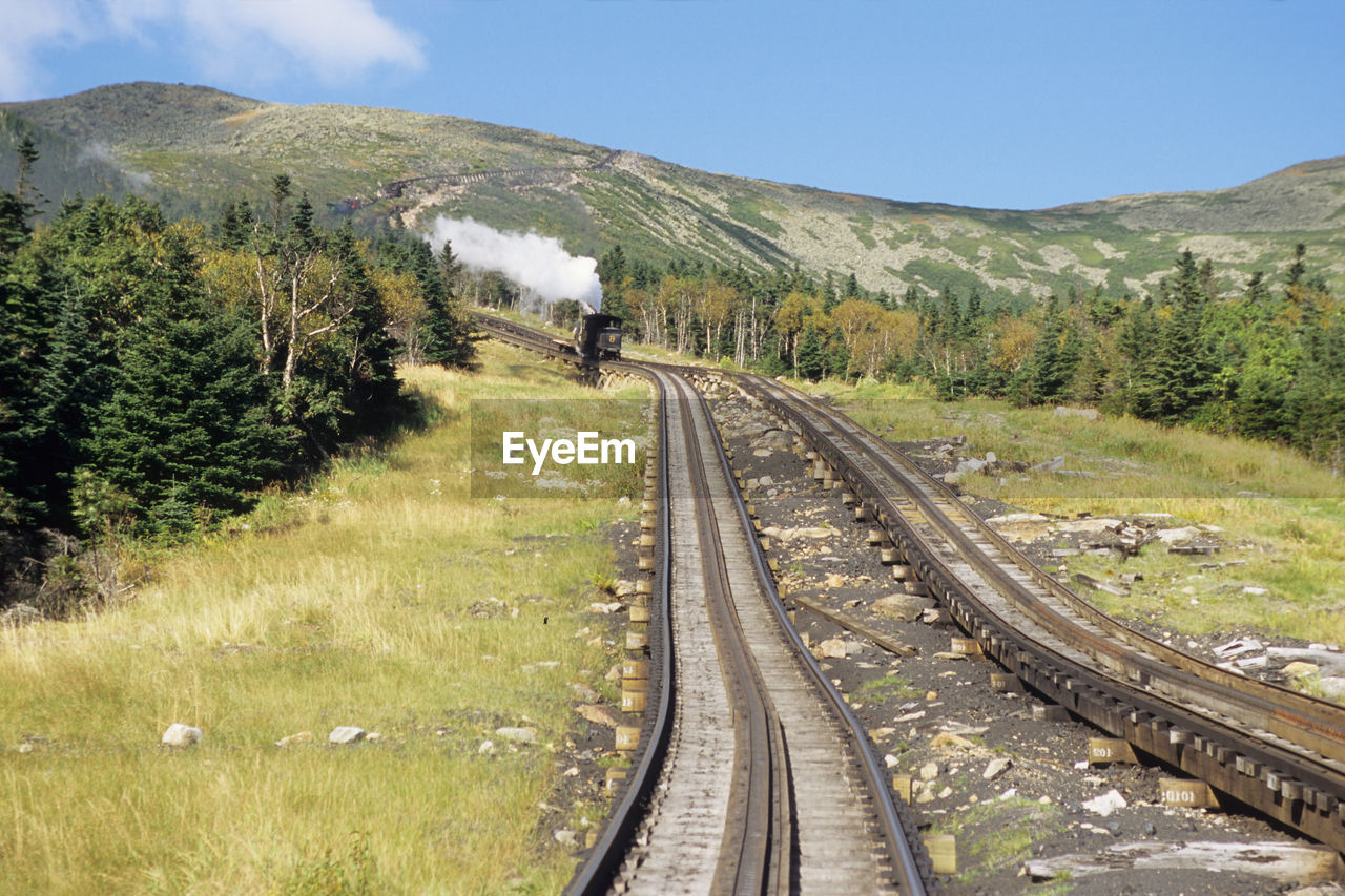 railroad track, track, rail transportation, transportation, plant, tree, nature, mode of transportation, the way forward, sky, direction, mountain, day, grass, one person, land, real people, public transportation, environment, scenics - nature, outdoors