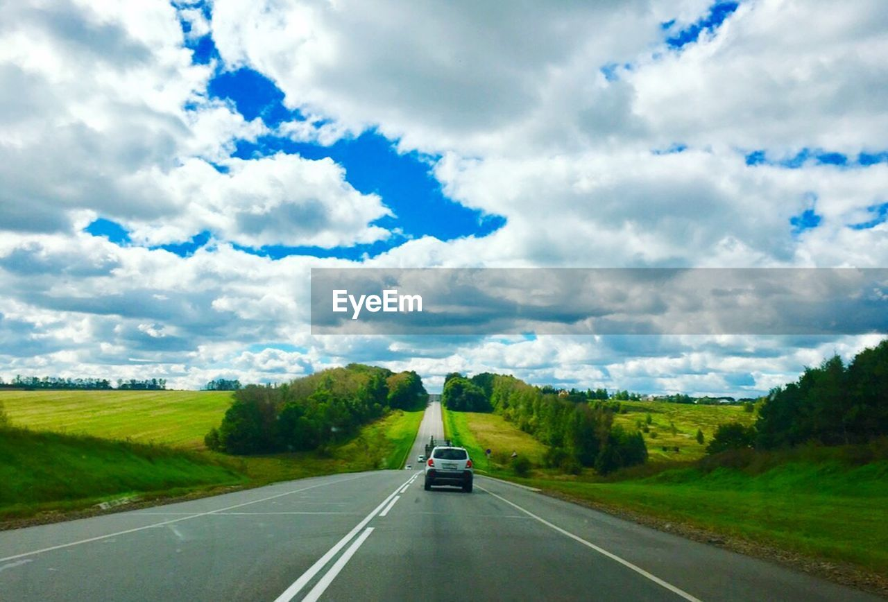 road, cloud - sky, transportation, sky, the way forward, scenics, day, nature, car, green color, landscape, no people, tranquility, land vehicle, outdoors, beauty in nature, tree, grass