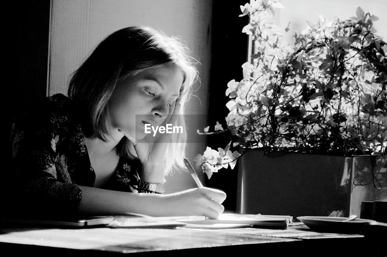 Woman Writing On Book At Table