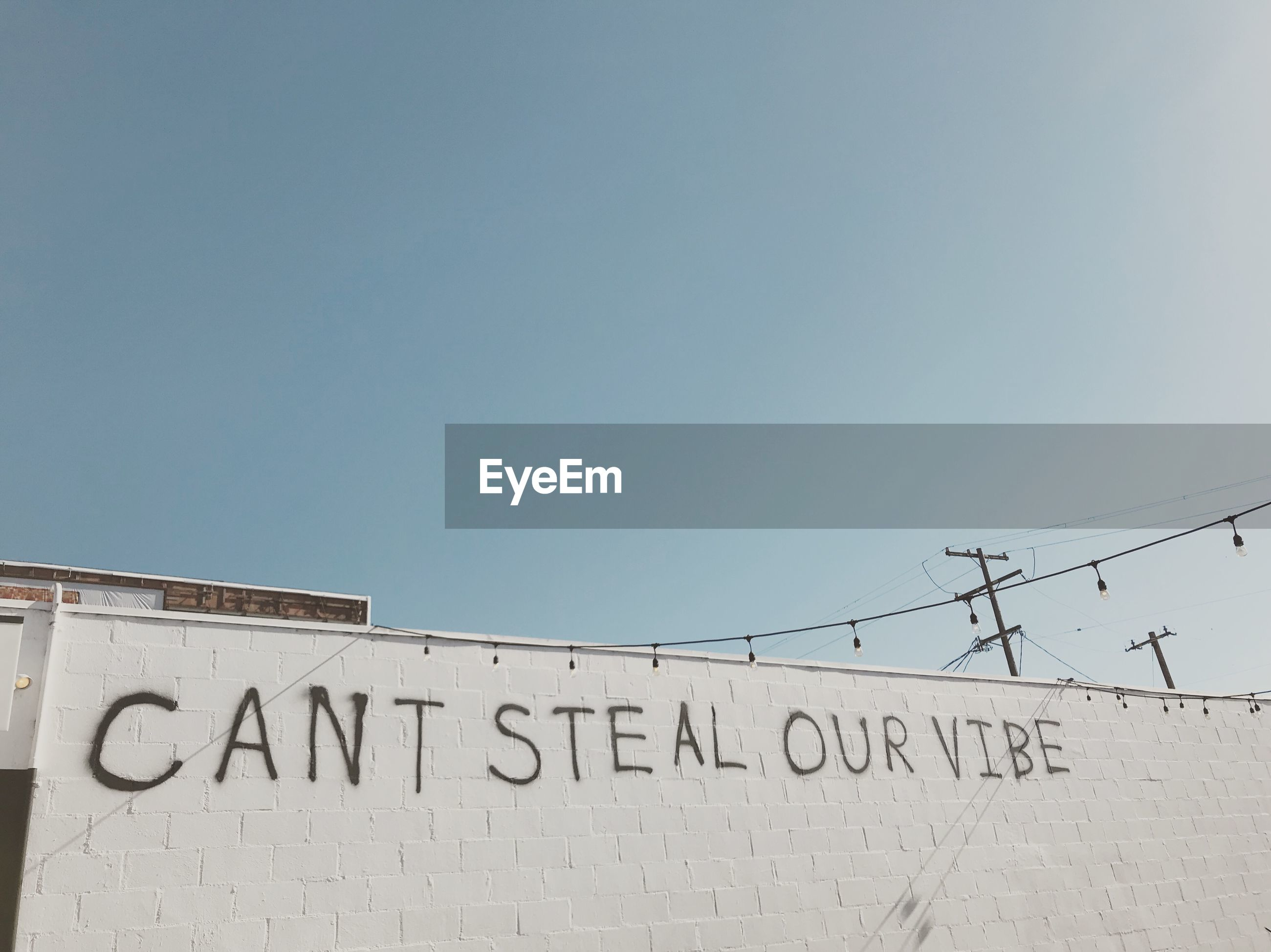 Low angle view of text on wall against clear sky