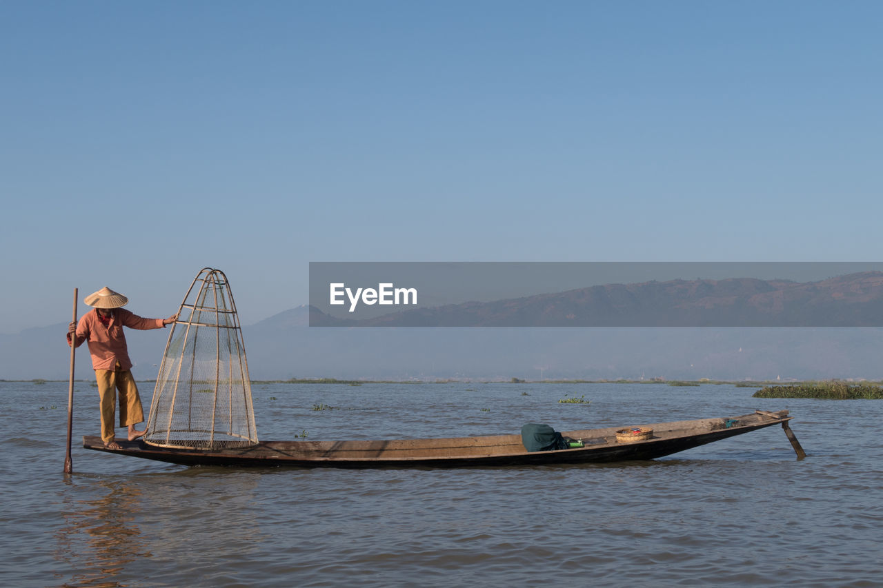 nautical vessel, water, real people, transportation, mode of transport, clear sky, outdoors, nature, fishing net, one person, day, mountain, beauty in nature, men, sky, people
