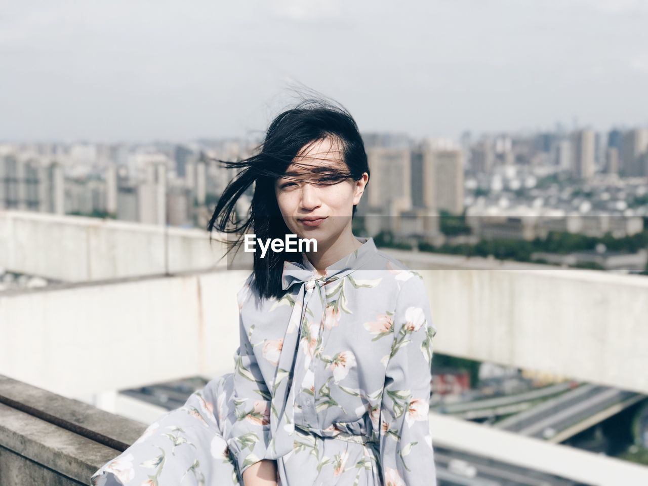 Young Woman Standing By Cityscape Against Sky