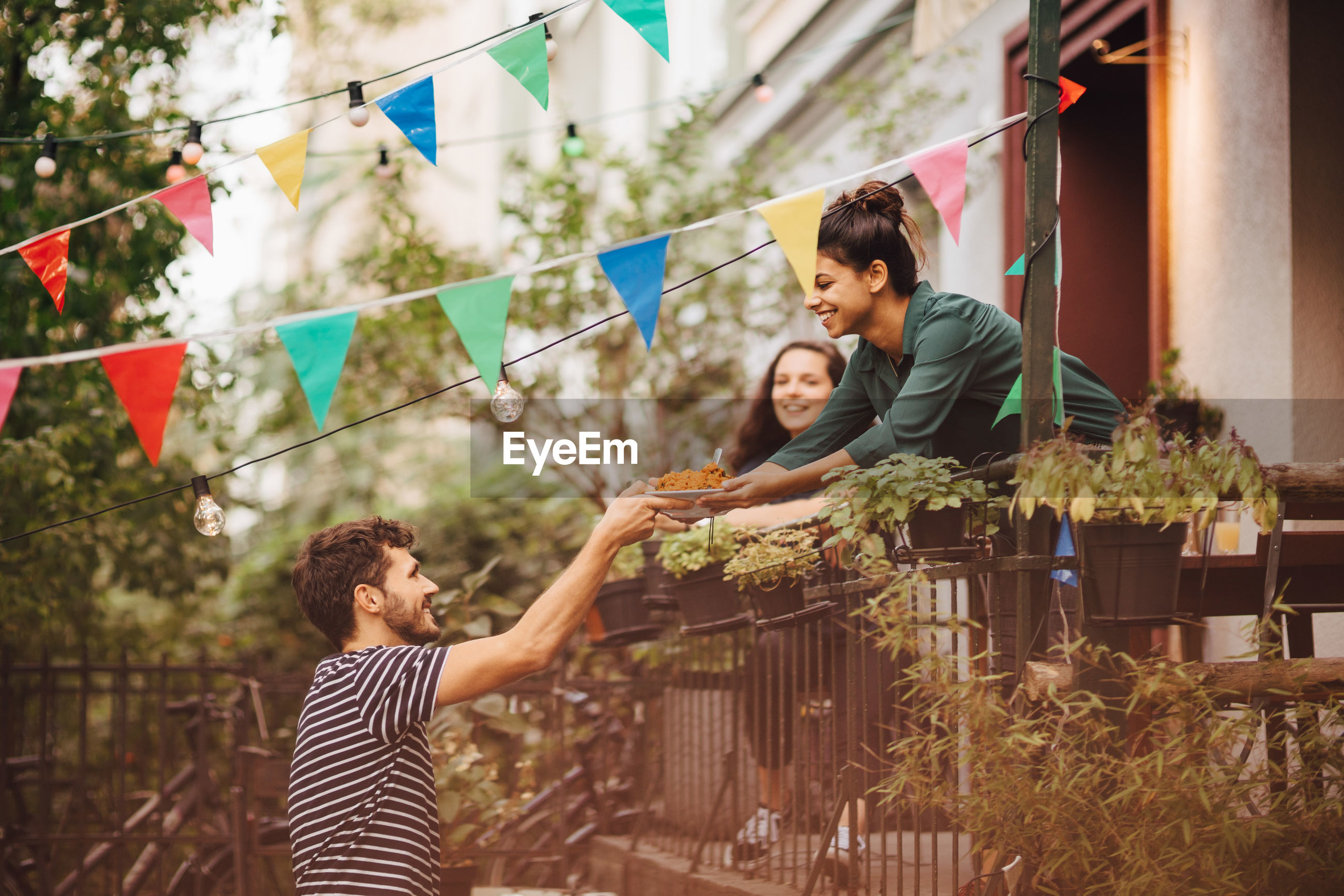 Smiling young woman giving food to male friend from balcony during garden party