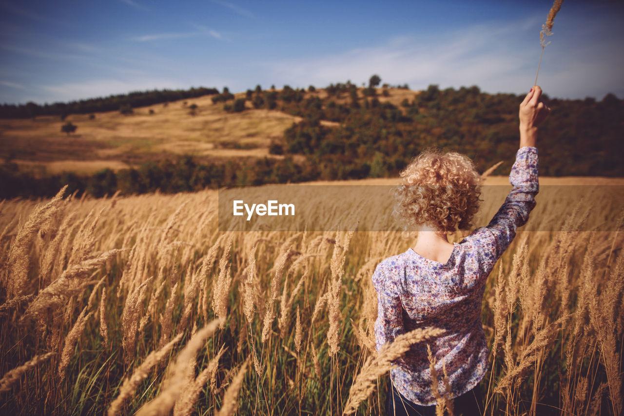 Rear View Of Woman In Farm Field Against Sky