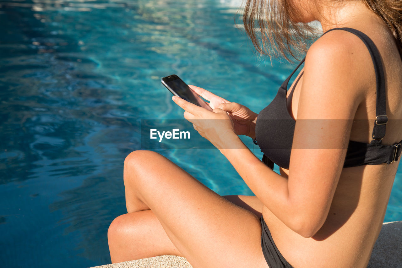 Midsection of woman using mobile phone in swimming pool